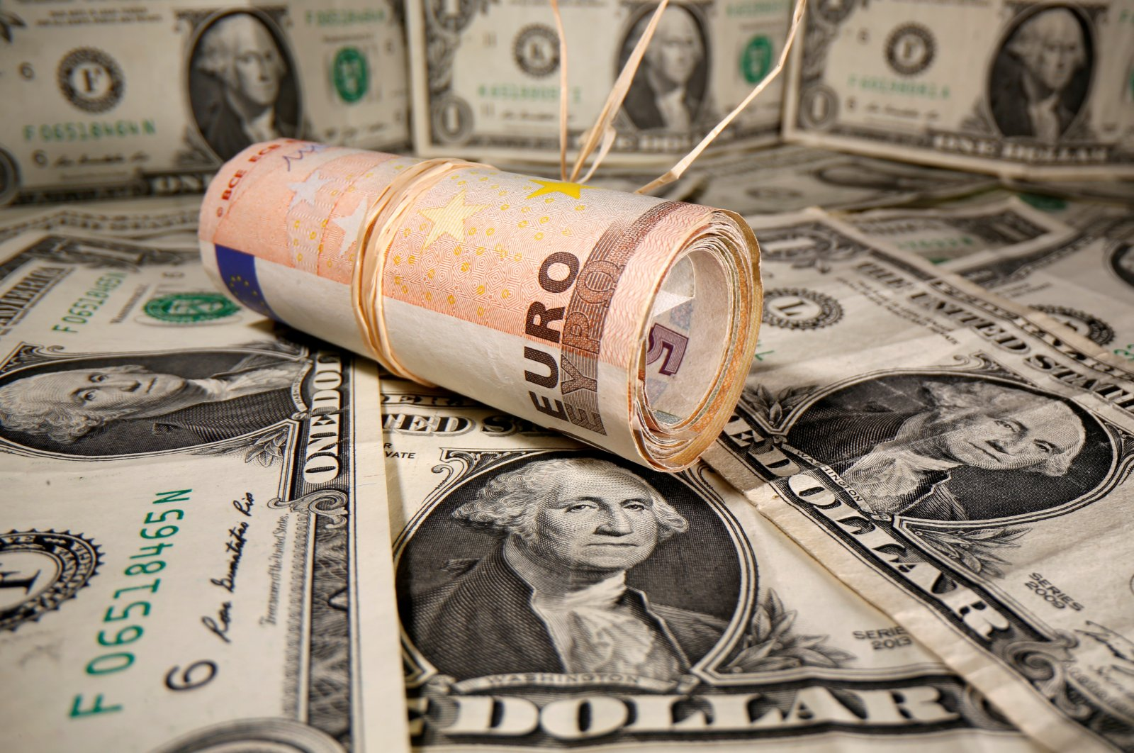 Rolled euro banknotes are placed on U.S. dollar banknotes in this illustration taken May 26, 2020. (Reuters Photo)