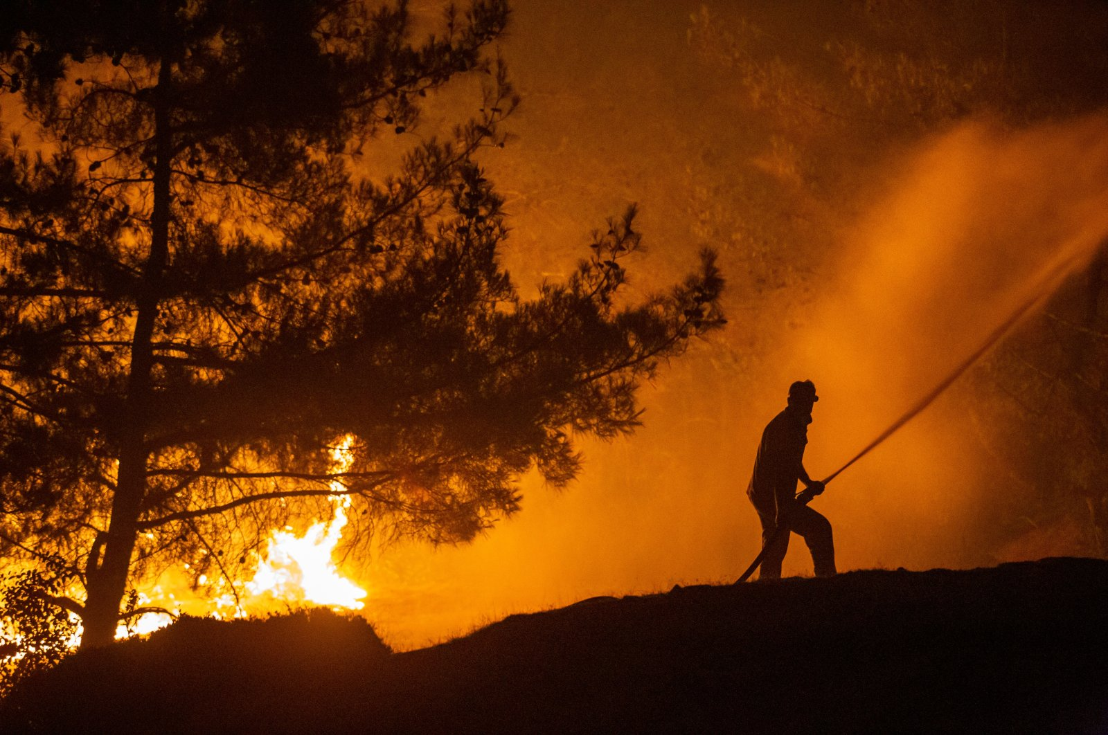 A firefighter sprays water on flames at a forest in Hatay, southern Turkey, July 16, 2021. (AA PHOTO)