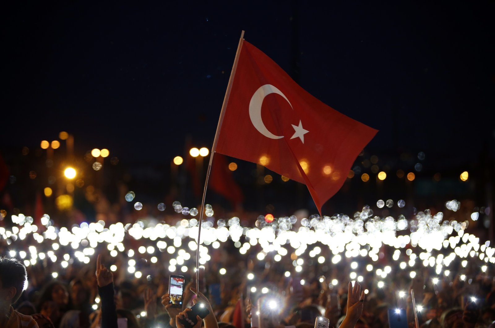 People use their mobile phones as flashlights as they attend a commemoration event for the second anniversary of the July 15 failed coup attempt, in Istanbul, Turkey, July 15, 2018. (AP Photo)