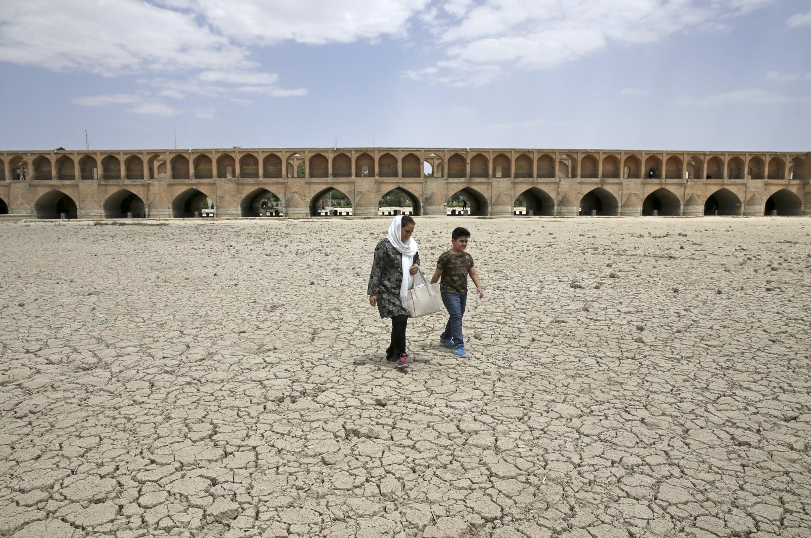 A woman and a boy walk on the dried-up riverbed of the Zayandeh Roud river near the 400-year old Si-o-Se Pol bridge, Isfahan, Iran, July 10, 2018. (AP Photo)