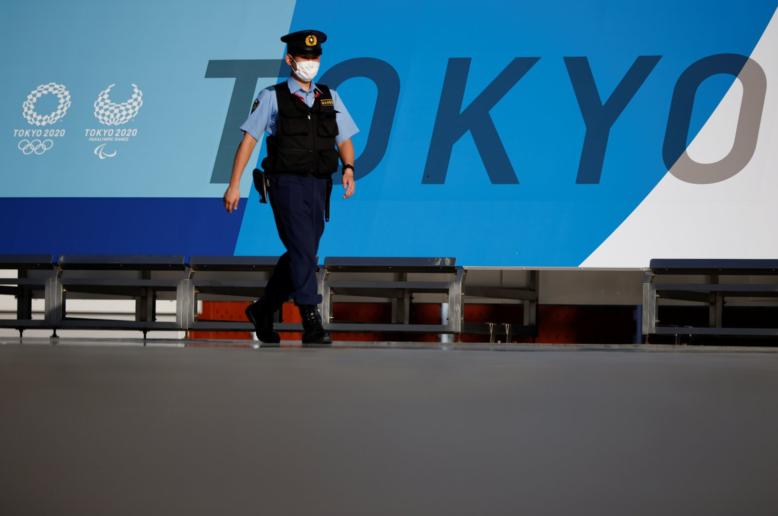 A police officer wearing a face mask walks past Tokyo 2020 Olympic Games signage at the Main Press Center during the coronavirus outbreak in Tokyo, Japan, July 16, 2021. (Reuters Photo)