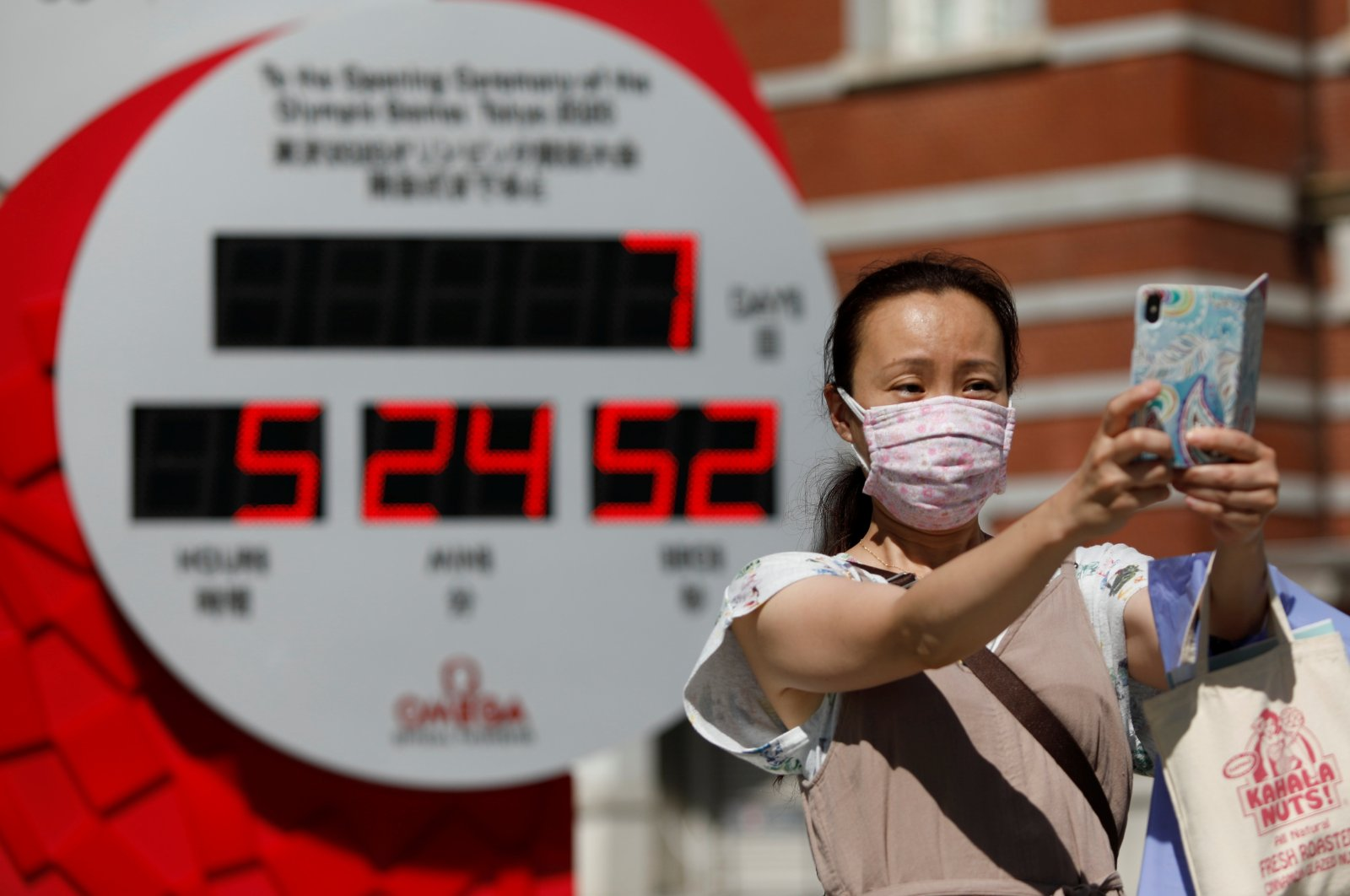 A woman takes a selfie in front of a Tokyo 2020 Olympic Games countdown clock in Tokyo, Japan, July 16, 2021. (Reuters Photo)