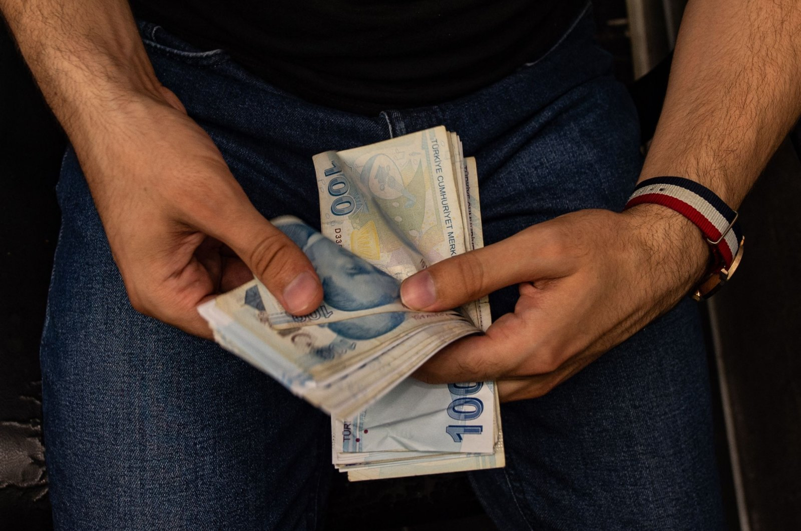 A currency exchange office worker counts Turkish Lira banknotes at an exchange office in Istanbul, Turkey, Aug. 6, 2020. (AFP Photo)