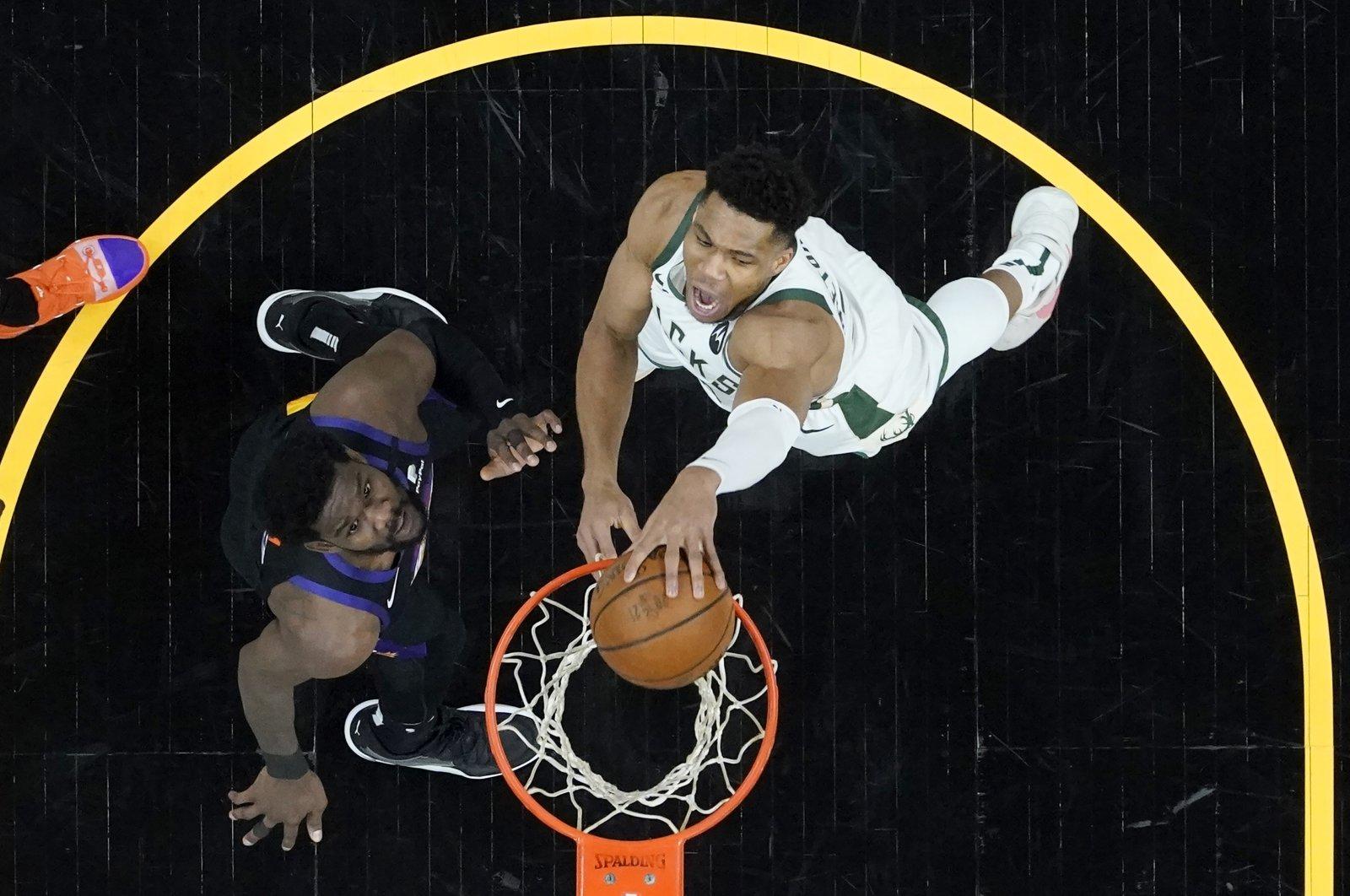 Milwaukee Bucks forward Giannis Antetokounmpo (R) dunks over Phoenix Suns center Deandre Ayton during Game 2 of NBA Finals, July 8, 2021, Phoenix, Arizona, U.S. (AP Photo)