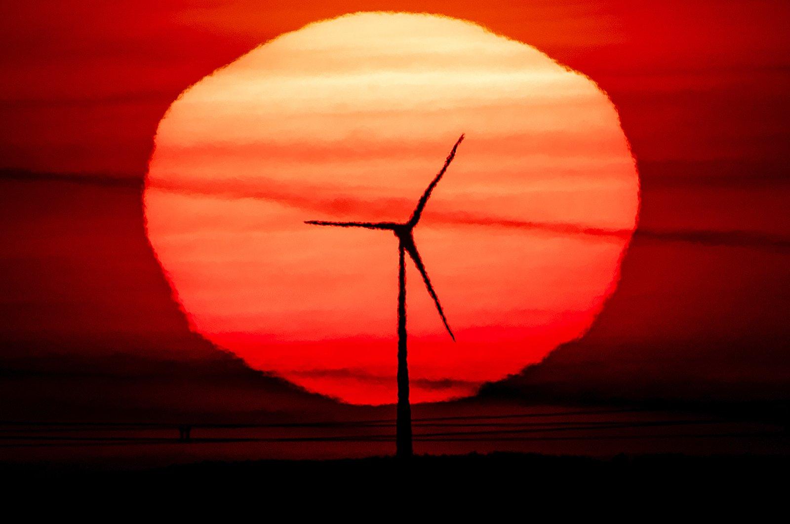 The sun rises behind a wind turbine in Frankfurt, Germany, Sept. 15, 2020. (AP File Photo/Michael Probst)