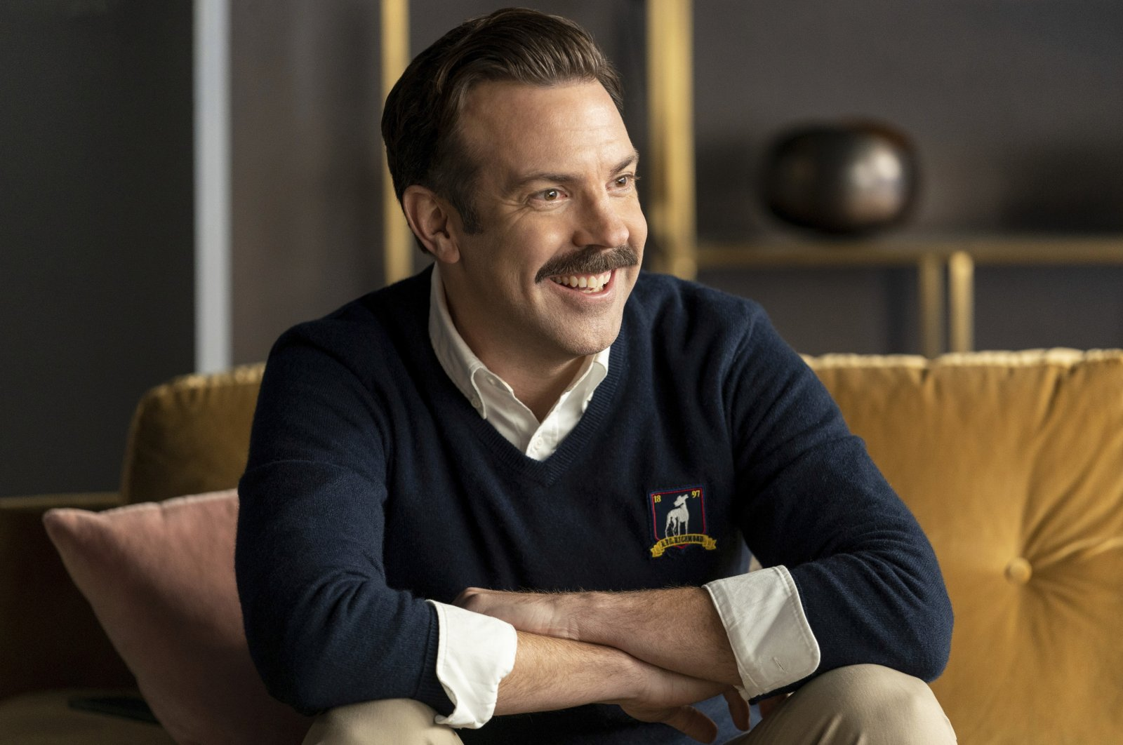 """Jason Sudeikis, as Ted Lasso, smiles as he sits on a sofa, in a scene from the series """"Ted Lasso."""" (Apple TV+ via AP)"""