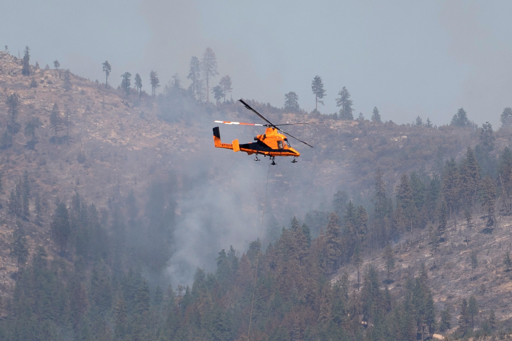 A helicopter carries water while fighting the Chuweah Creek Fire as wildfires devastate Nespelem in eastern Washington state, U.S., July 16, 2021.  (Reuters Photo)