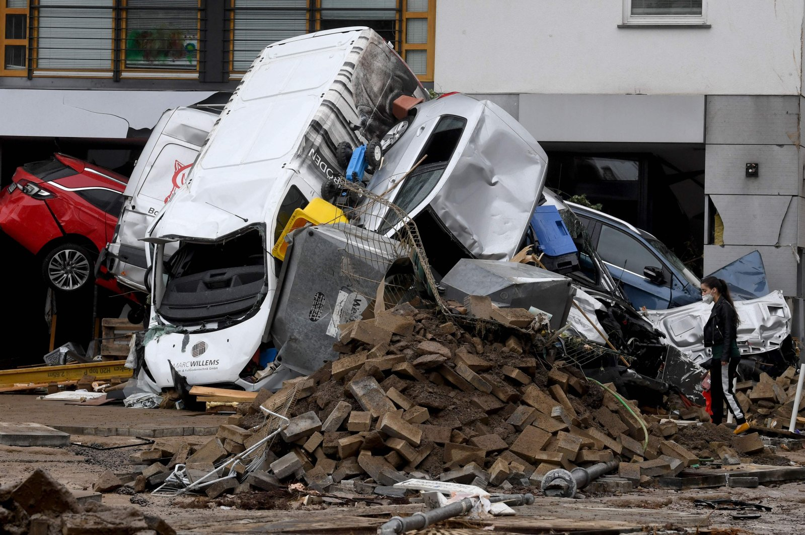 A woman looks at cars and rubble piled up in a street after the floods caused major damage in Bad Neuenahr-Ahrweiler, western Germany, July 16, 2021. (AFP Photo)