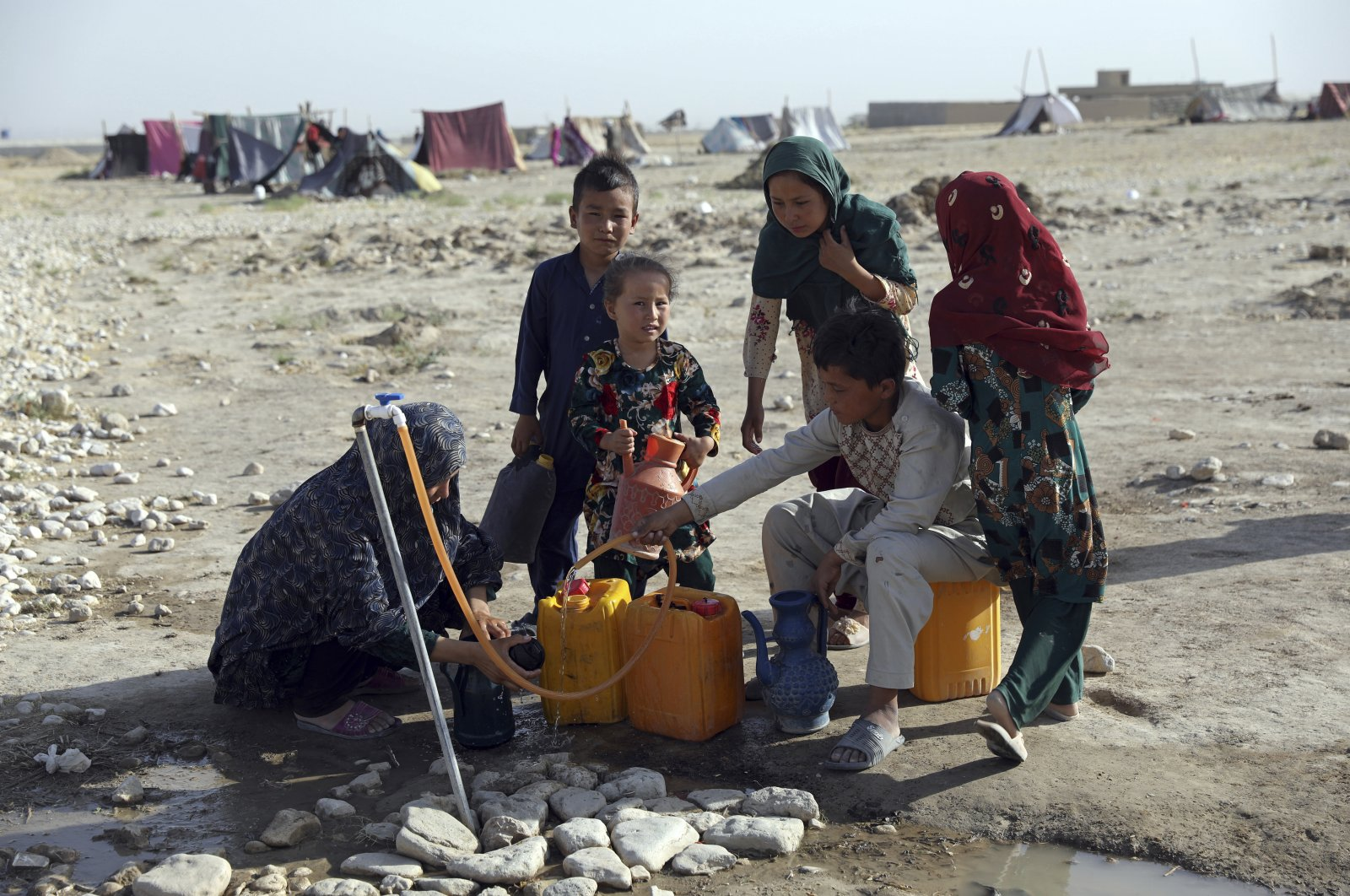 Internally displaced Afghans, who fled their home due to fighting between the Taliban and Afghan security personnel, fill water containers from a public water tap at a camp on the outskirts of Mazar-e-Sharif, northern Afghanistan, July 8, 2021. (AP Photo)