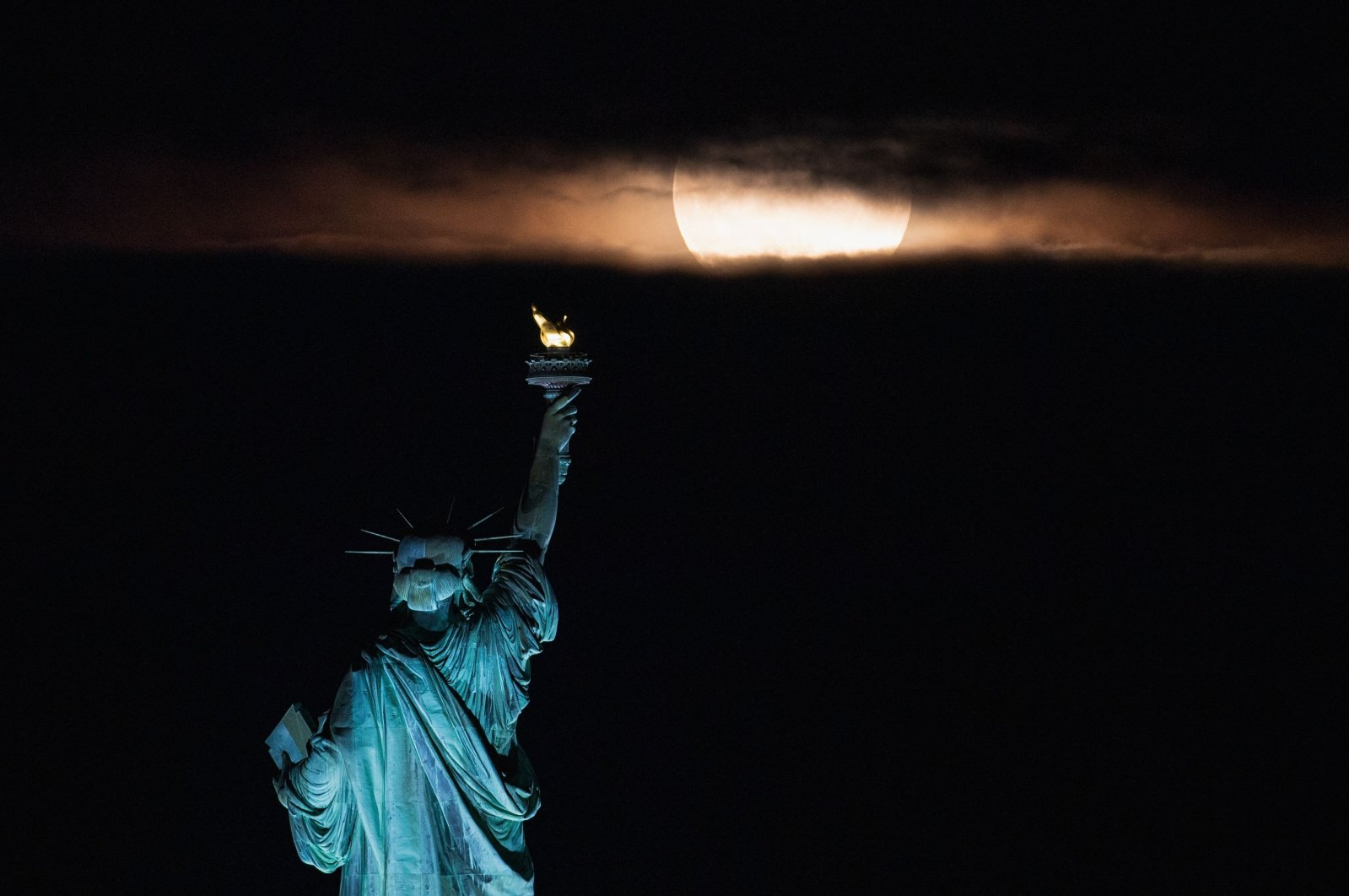 The full moon, known as the strawberry moon, rises behind the Statue of Liberty in New York City, U.S., June 24, 2021. (AFP Photo)