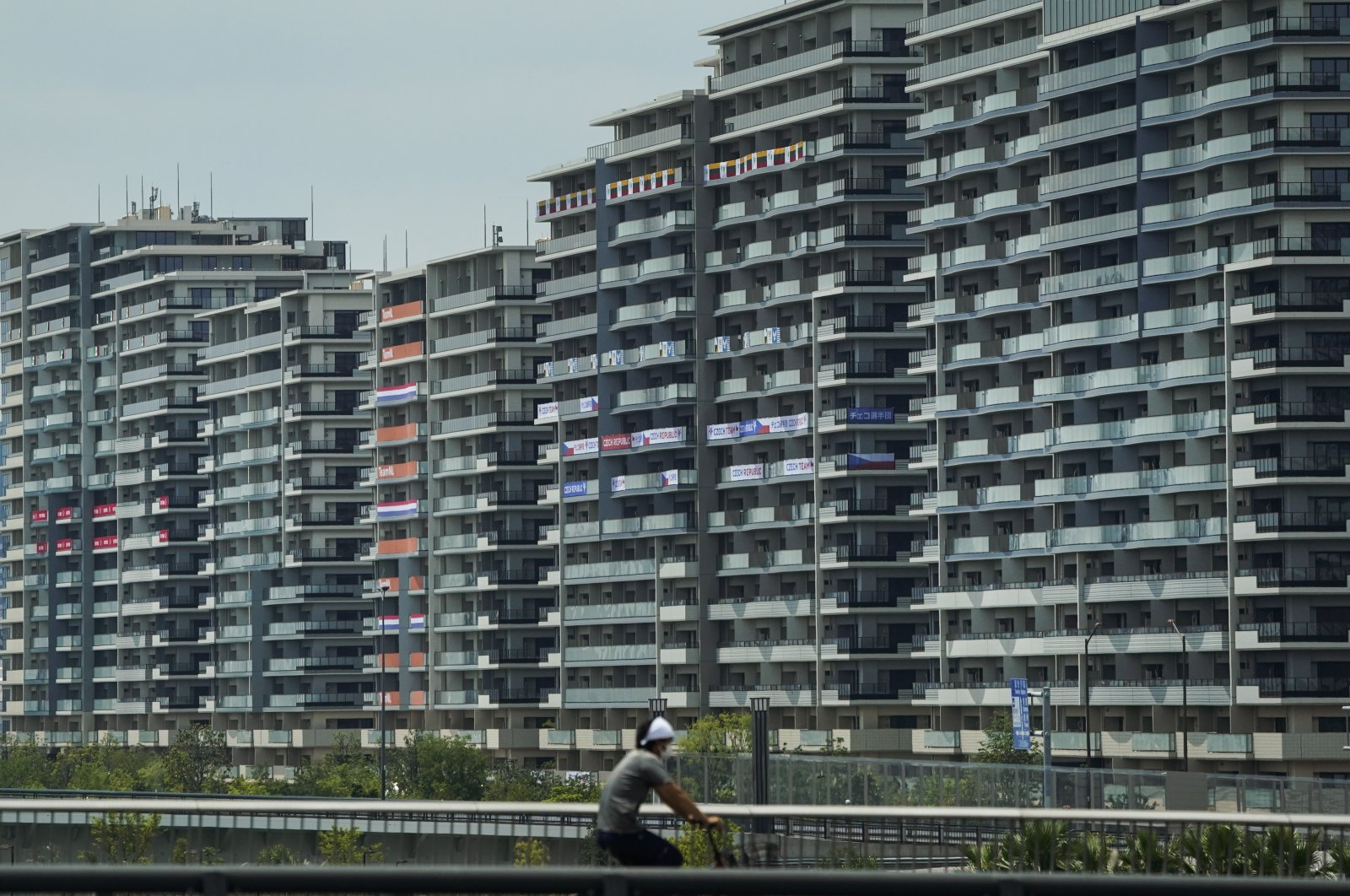 A man rides his bike near the athlete's village for the 2020 Summer Olympics and Paralympics, in Tokyo, Japan, July 15, 2021. (AP Photo)