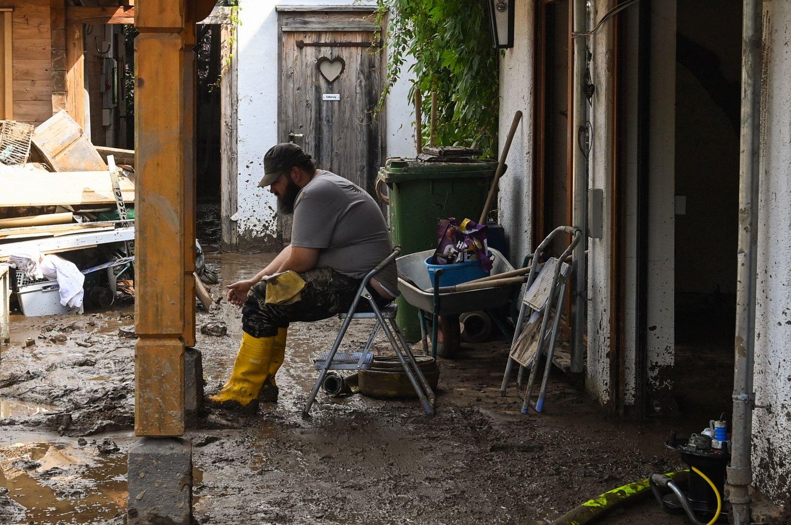 A man rests in a muddied courtyard in Insul near Bad Neuenahr-Ahrweiler, western Germany, on July 17, 2021. (AFP Photo)