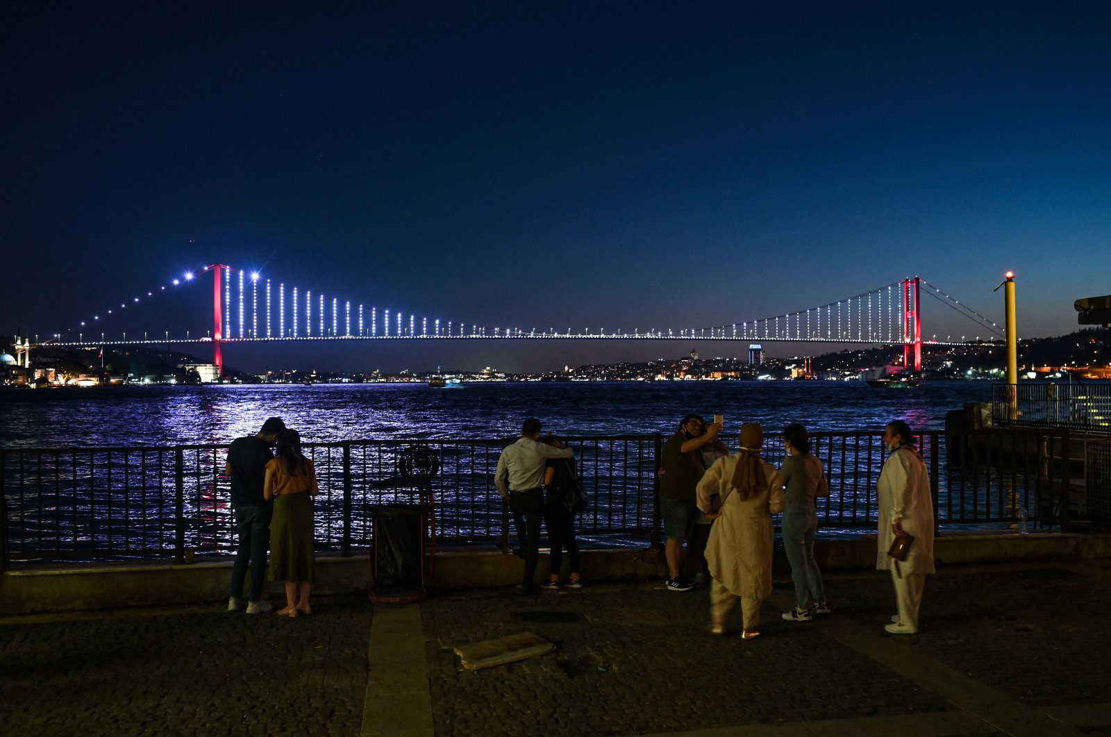 People stand in front of the 15 July Martyrs Bridge, known as the Bosporus Bridge, in Istanbul, Turkey, July 16, 2021. (AFP Photo)
