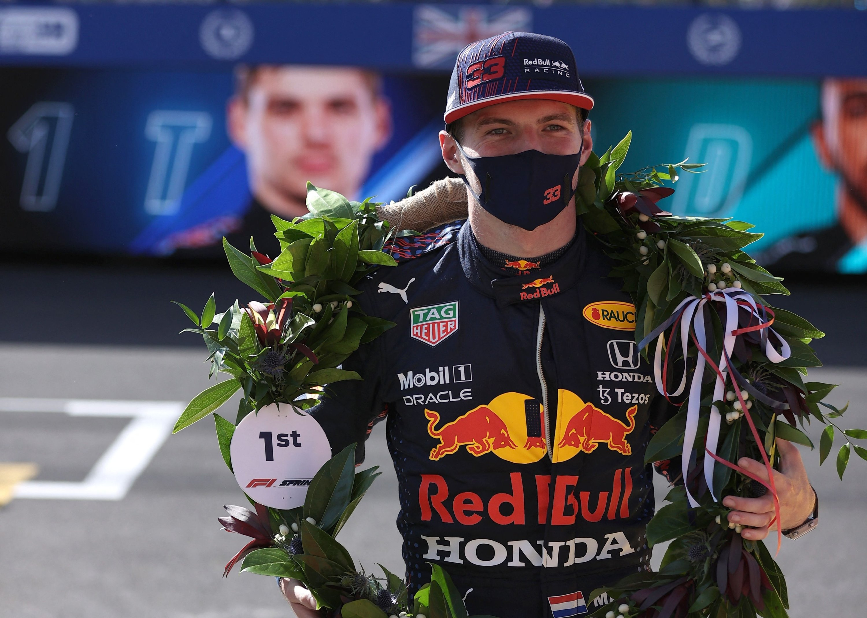 Red Bull's Dutch driver Max Verstappen wears the winner's laurel wreath as he celebrates attaining pole position for the Formula One British Grand Prix at the Silverstone Circuit, Silverstone, central England, July 17, 2021. (AFP Photo)