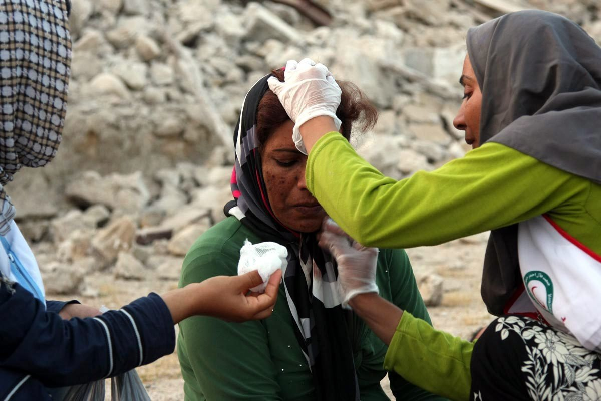 Iranian Red Crescent workers try to help a victim of the earthquake in Shonbeh Twon, Bushehr province in southern Iran, April 9, 2013. (EPA File Photo)