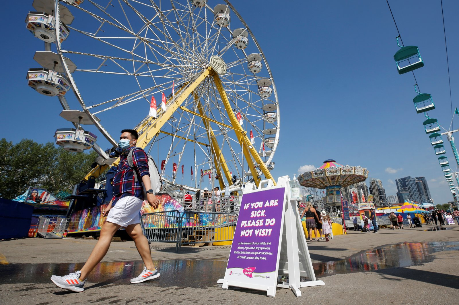 A man wearing a face mask walks by a health safety sign as the Calgary Stampede gets underway following a year off due to COVID-19 restrictions, Alberta, Canada, July 9, 2021. (Reuters Photo)