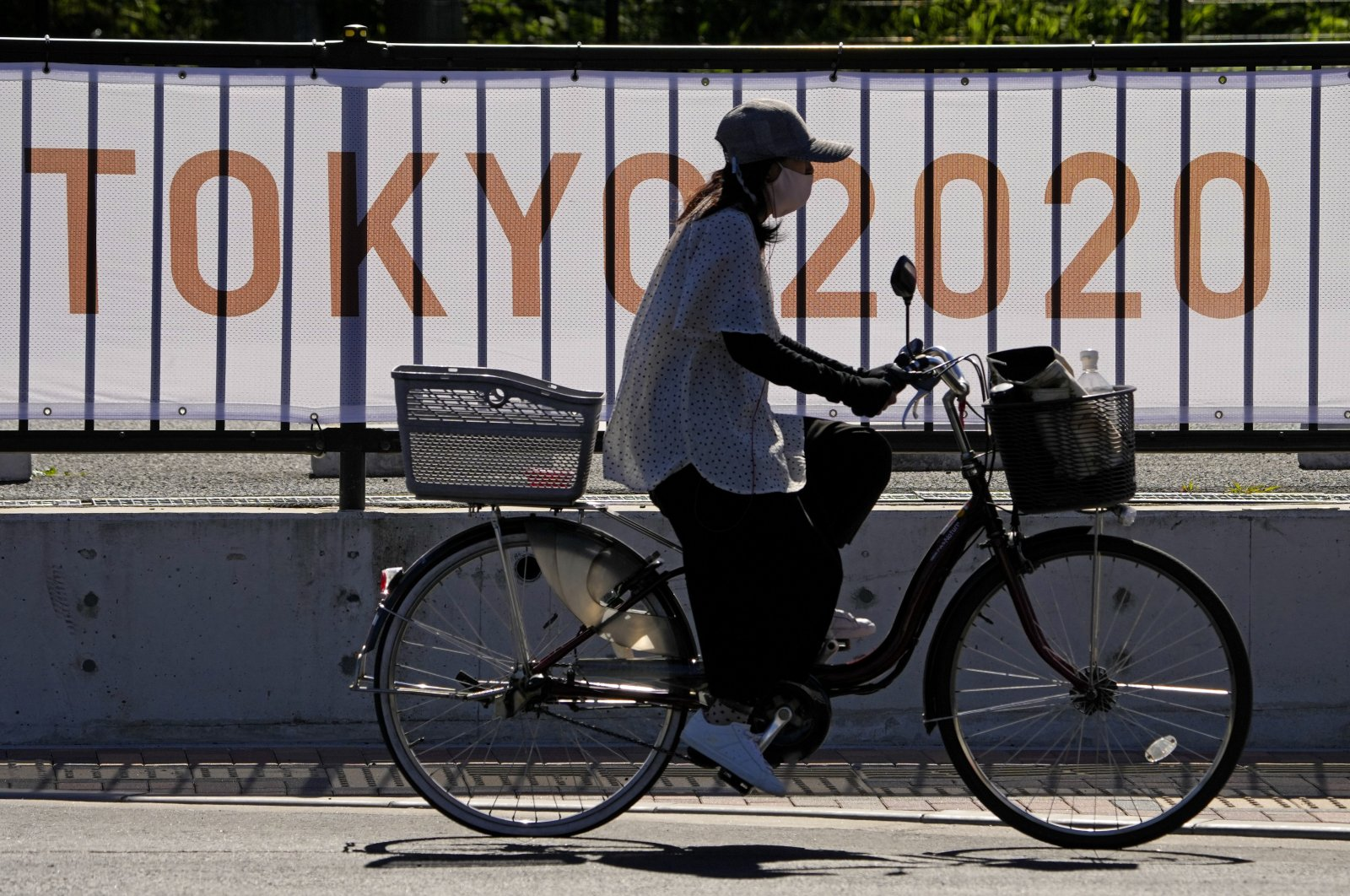 A woman rides her bike past signage for the 2020 Summer Olympics, Tokyo, Japan, July 18, 2021. (AP Photo)