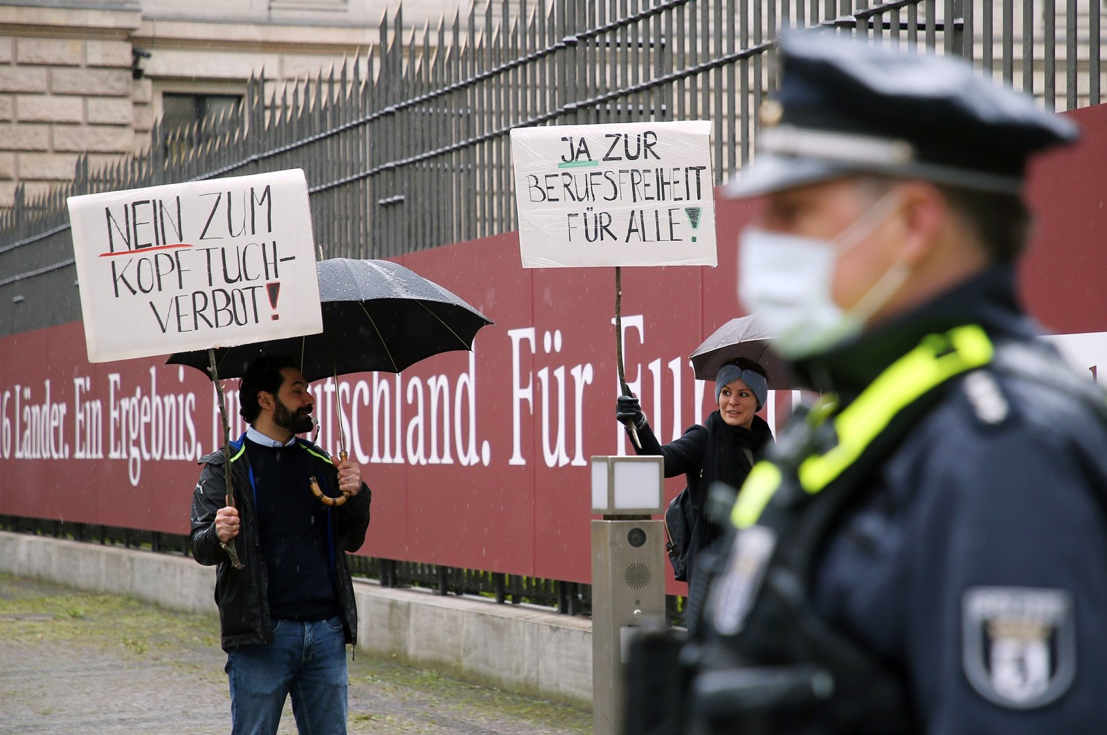 Two demonstrators hold up a sign in front of the Federal Council against a headscarf ban, Berlin, Germany, May 7, 2021, Berlin (Getty Images)