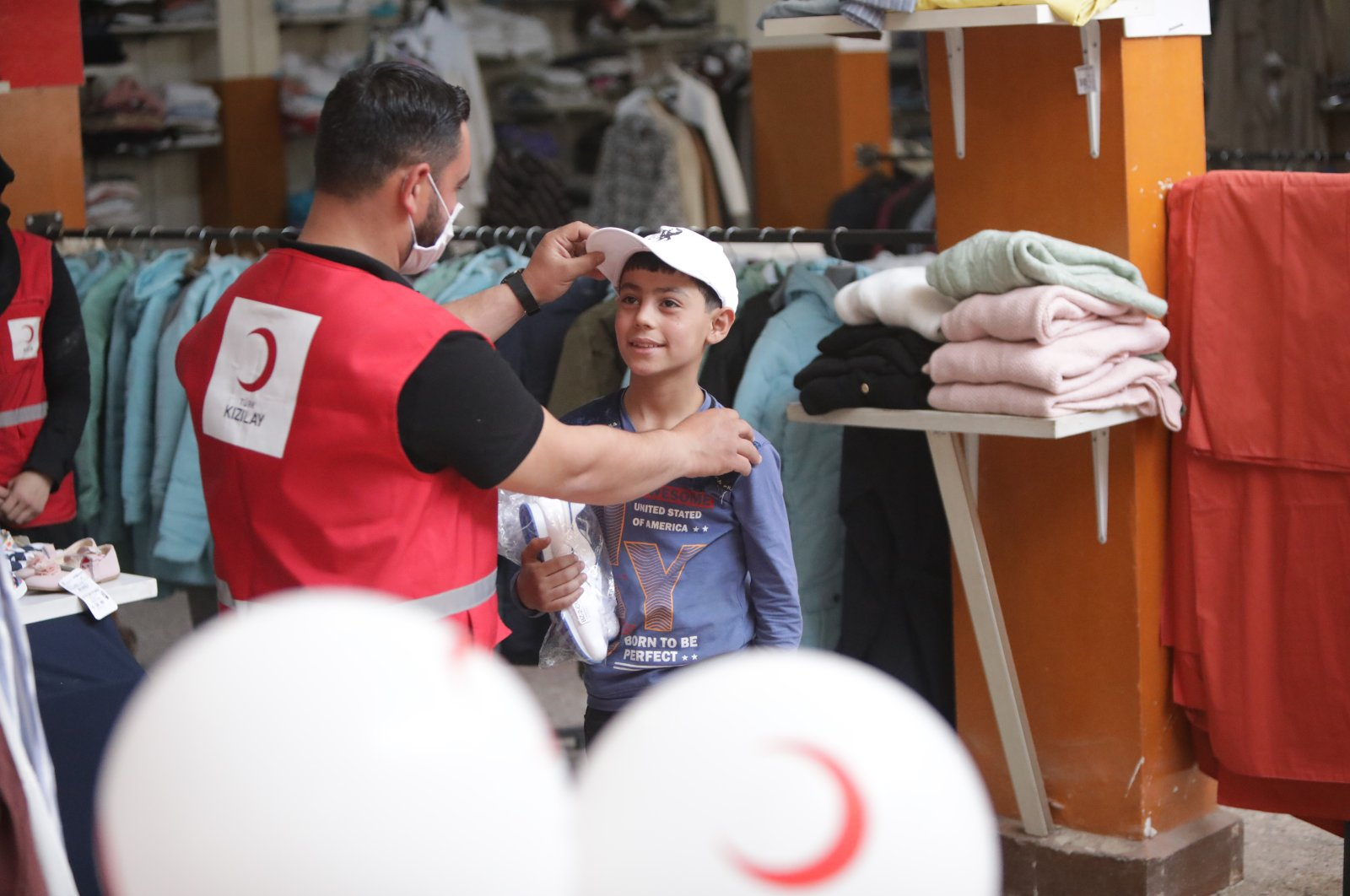 A Turkish Red Crescent worker gives new clothes to a Syrian boy, in Azaz, Syria, July 18, 2021. (AA PHOTO)