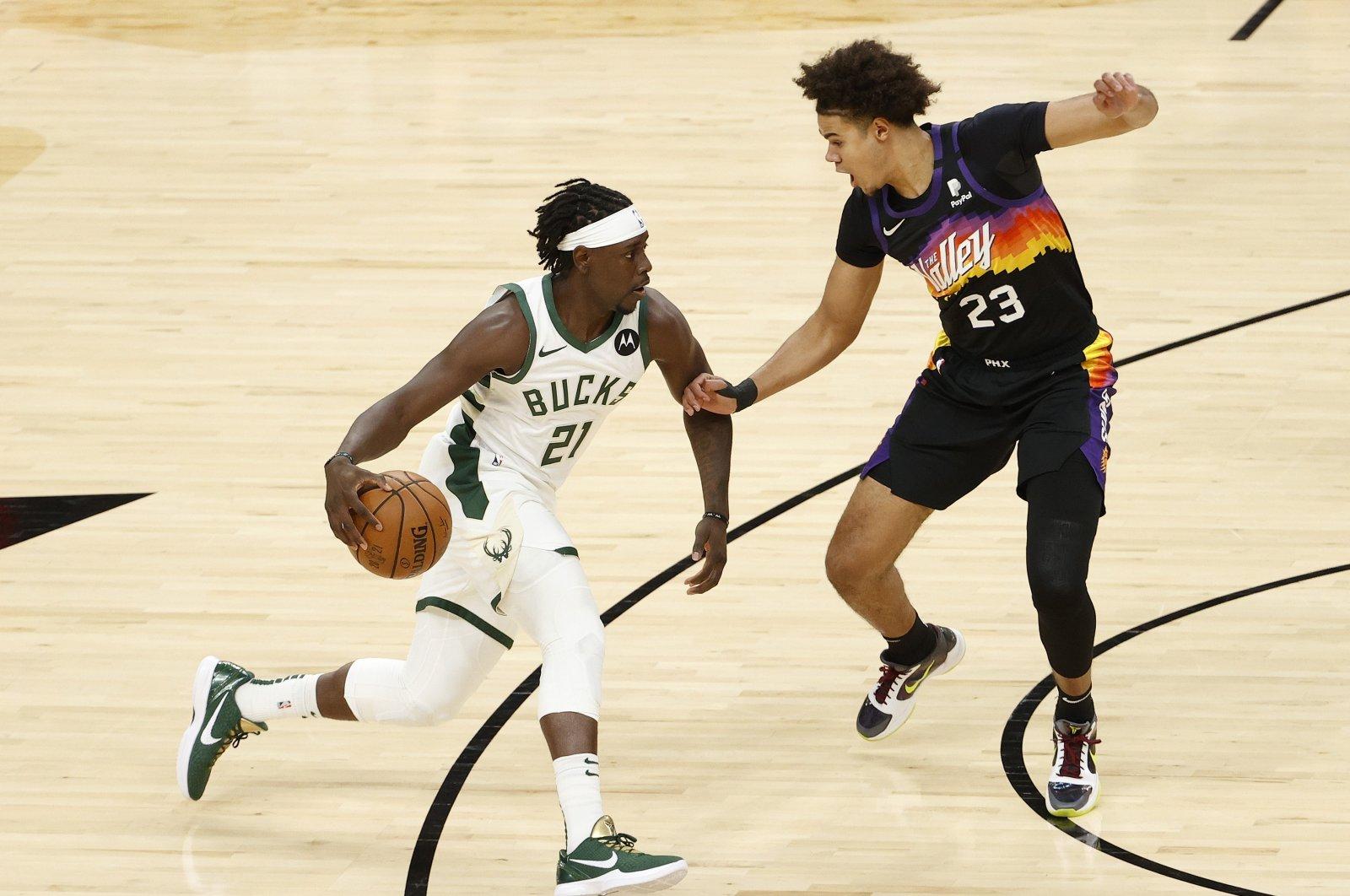 Milwaukee Bucks guard Jrue Holiday (L) brings the ball up court against Phoenix Suns' Cameron Johnson during NBA Finals Game 5 at Footprint Center, in Phoenix, Arizona, July 17, 2021. (AFP Photo)