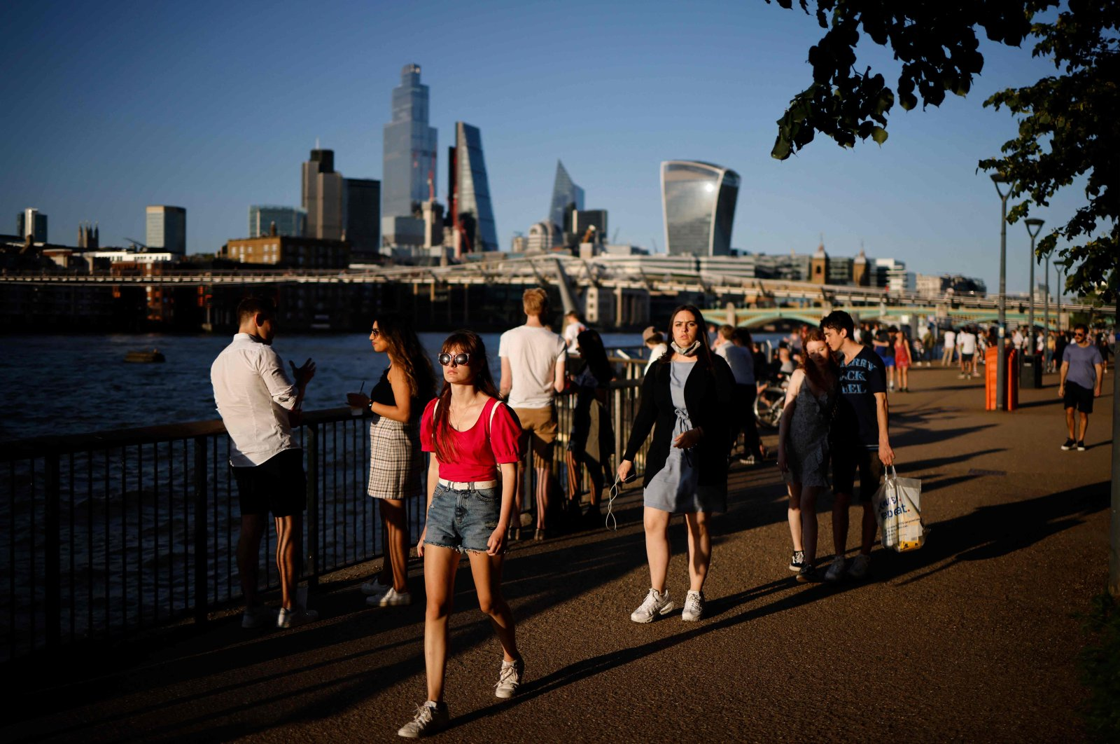 People enjoy the evening sunshine on Thames Embankment by the river Thames with the skyline of the City of London in the background, London, U.K., July 16, 2021. (AFP Photo)
