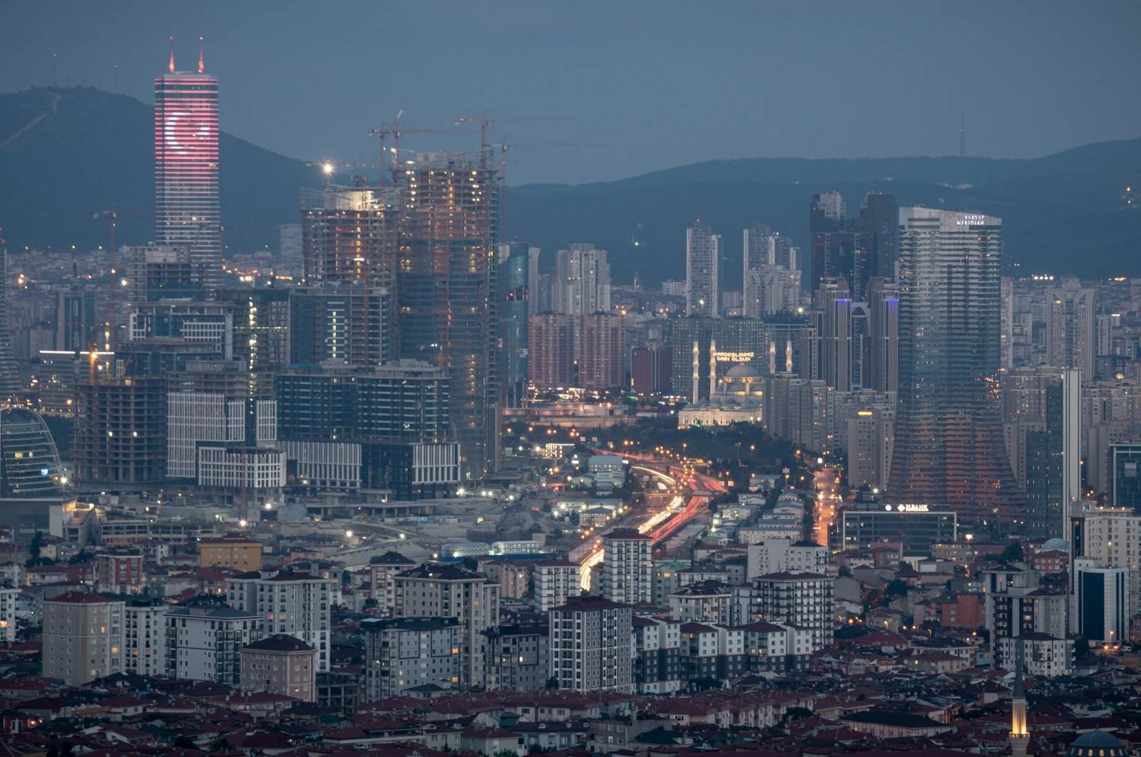 A skyscraper bares the Turkish flag in neon lights over a highly developed urban landscape with new construction projects and towers rising quickly, Istanbul, Turkey, July 11, 2021. (Photo by Getty Images)
