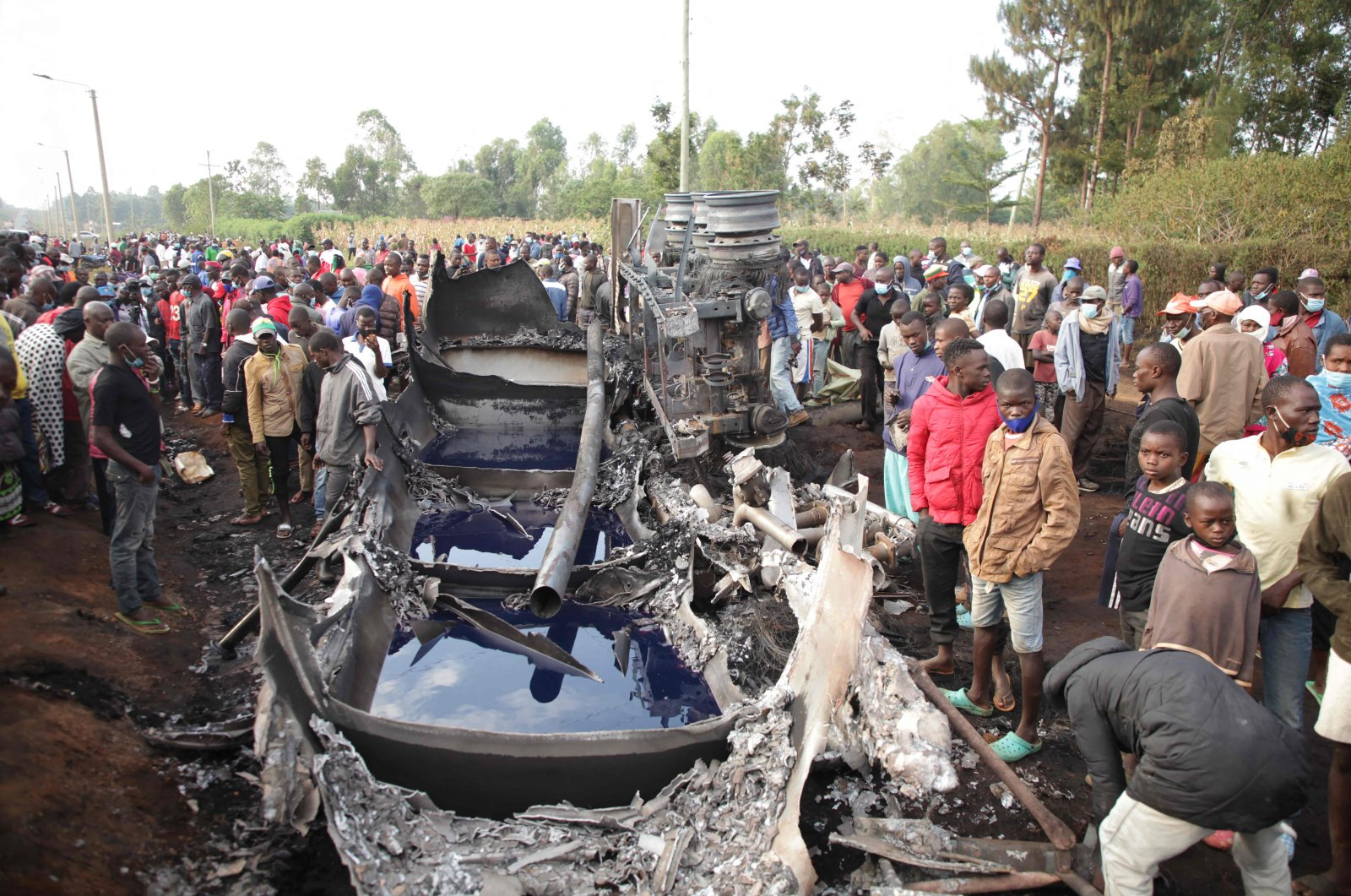 People stand next to a burnt-out petrol tanker that burst into flames when it overturned in western Kenya, while a crowd thronged to collect the spilling fuel, July 18, 2021. (AFP Photo)