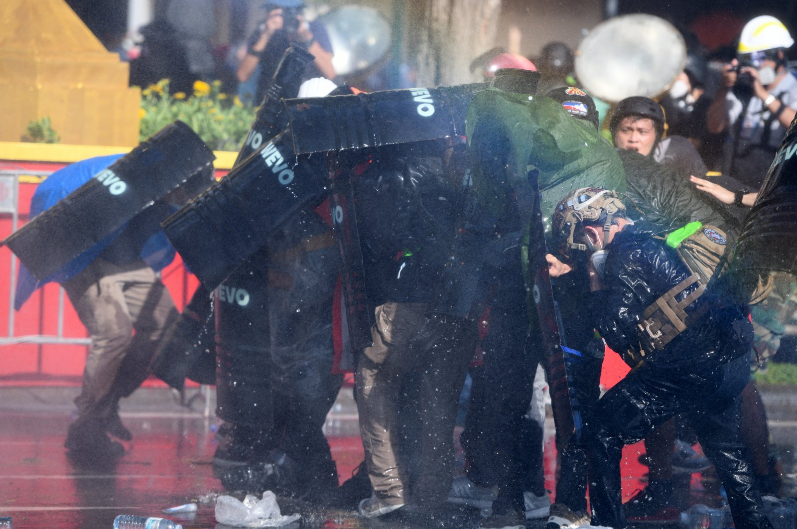 Anti-government protesters take cover as riot police spray them with a water cannon during a march toward Government House, demanding Thai Prime Minister Prayuth Chan-O-Cha's resignation, a mandatory vaccination policy and reform in the monarchy, Bangkok, Thailand, July 18, 2021. (Reuters Photo)