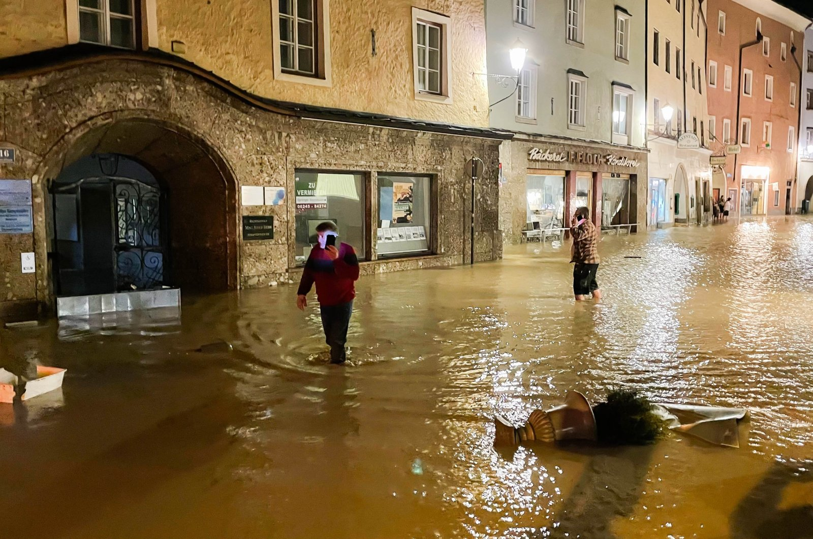 People walk in the flooded historic center, in Hallein, Austria, July 17, 2021. (AFP PHOTO)