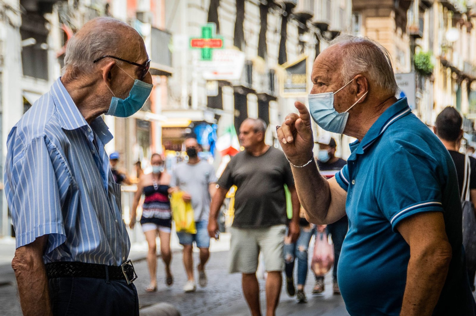 People stroll outdoors on the first day after Italy was classified as a white zone, in Naples, Italy, June 28, 2021. (EPA Photo)