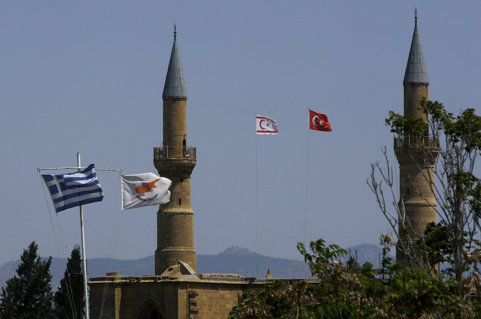 A Turkish and Turkish Republic of Northern Cyprus (TRNC) flags fly on a minaret of the Selimiye mosque, or Cathedral of St Sophia (Agia Sofia) behind Greek (L) and Greek Cypriot flags (2nd L) in divided capital Nicosia, Cyprus, Monday, April 26, 2021. (AP Photo/Petros Karadjias)