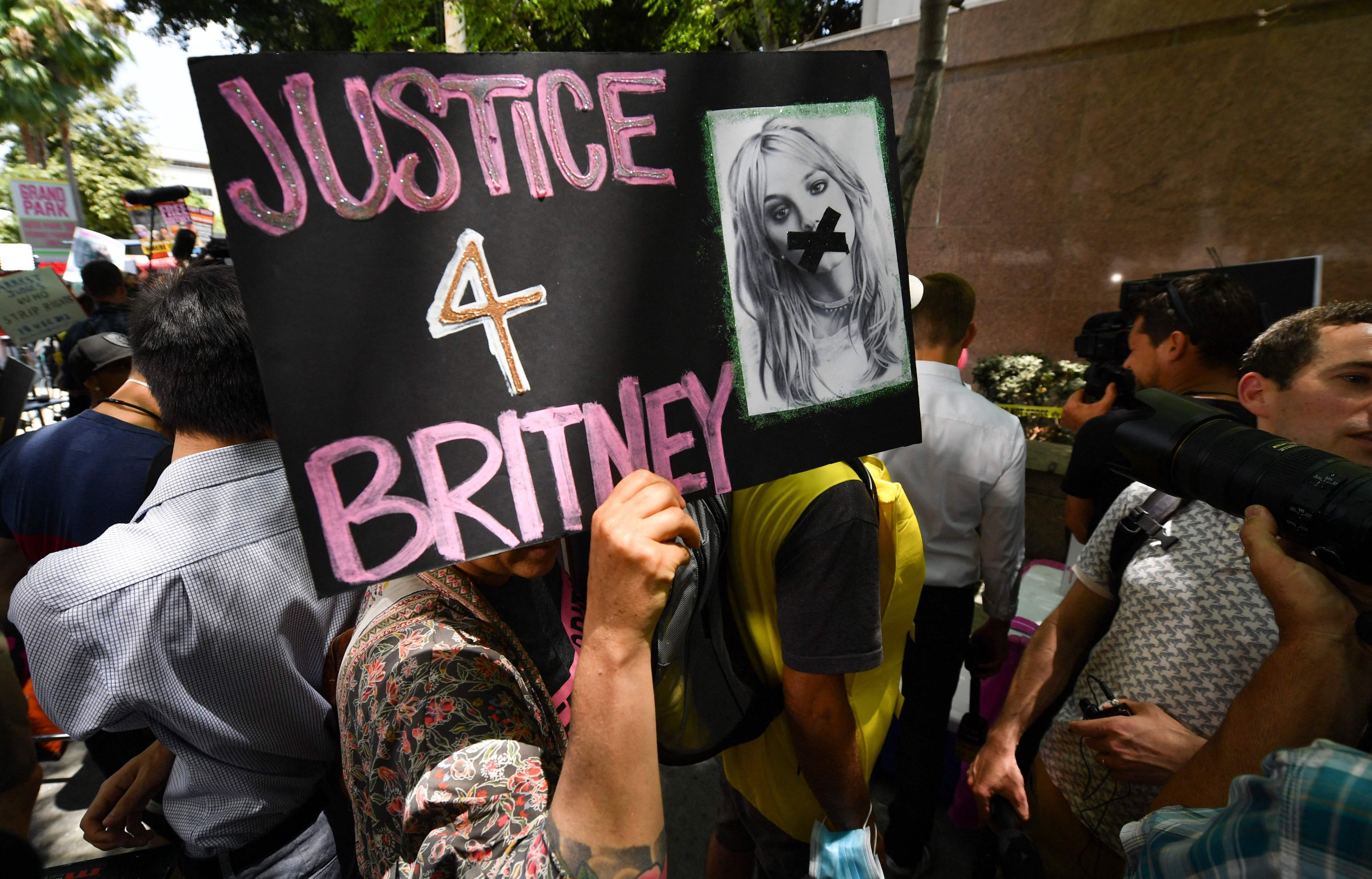 In this file photo a fan holds a poster of Britney with her mouth taped shut as supporters gather outside the Los Angeles County Courthouse in Los Angeles on July 14, 2021, during a scheduled hearing in the Britney Spears guardianship case. (AFP Photo)