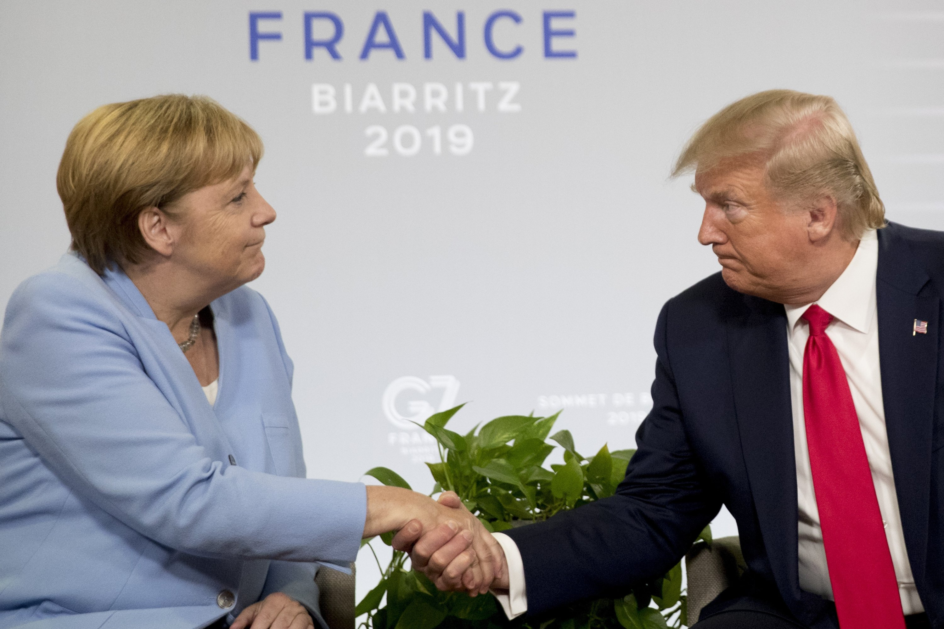 Then U.S. President Donald Trump (R) and German Chancellor Angela Merkel shake hands during a bilateral meeting at the G-7 summit in Biarritz, France, Aug. 26, 2019. (AP Photo)