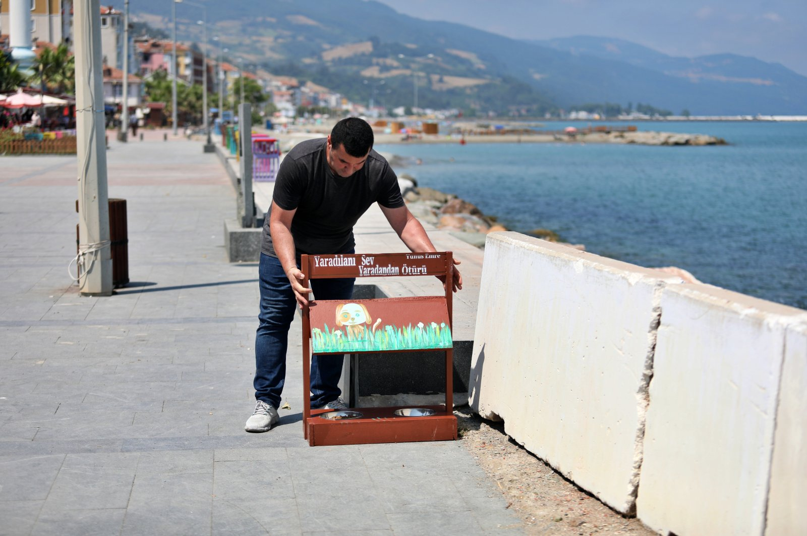 A worker places a feeder made of blackboards at the Yakakent shore, in Samsun, northern Turkey, July 18, 2021. (AA PHOTO)