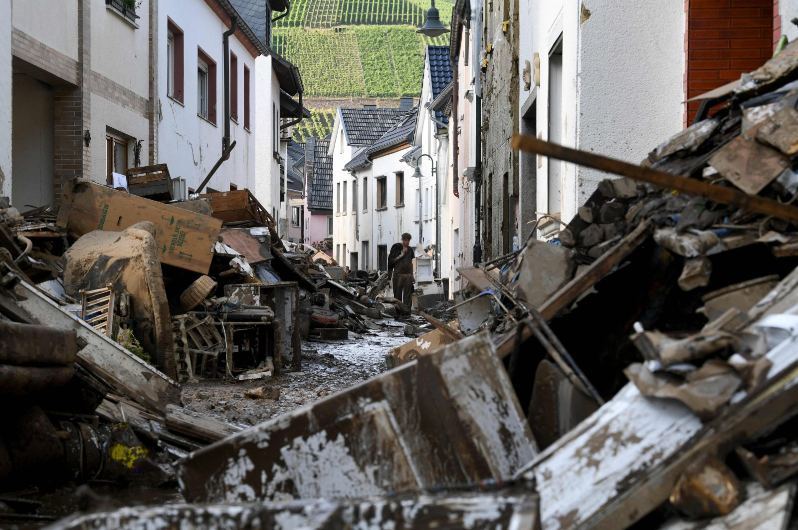 A resident walks in a muddy street full of debris and destroyed furniture after devastating floods in the city of Dernau, western Germany, on July 18, 2021. (AFP Photo)