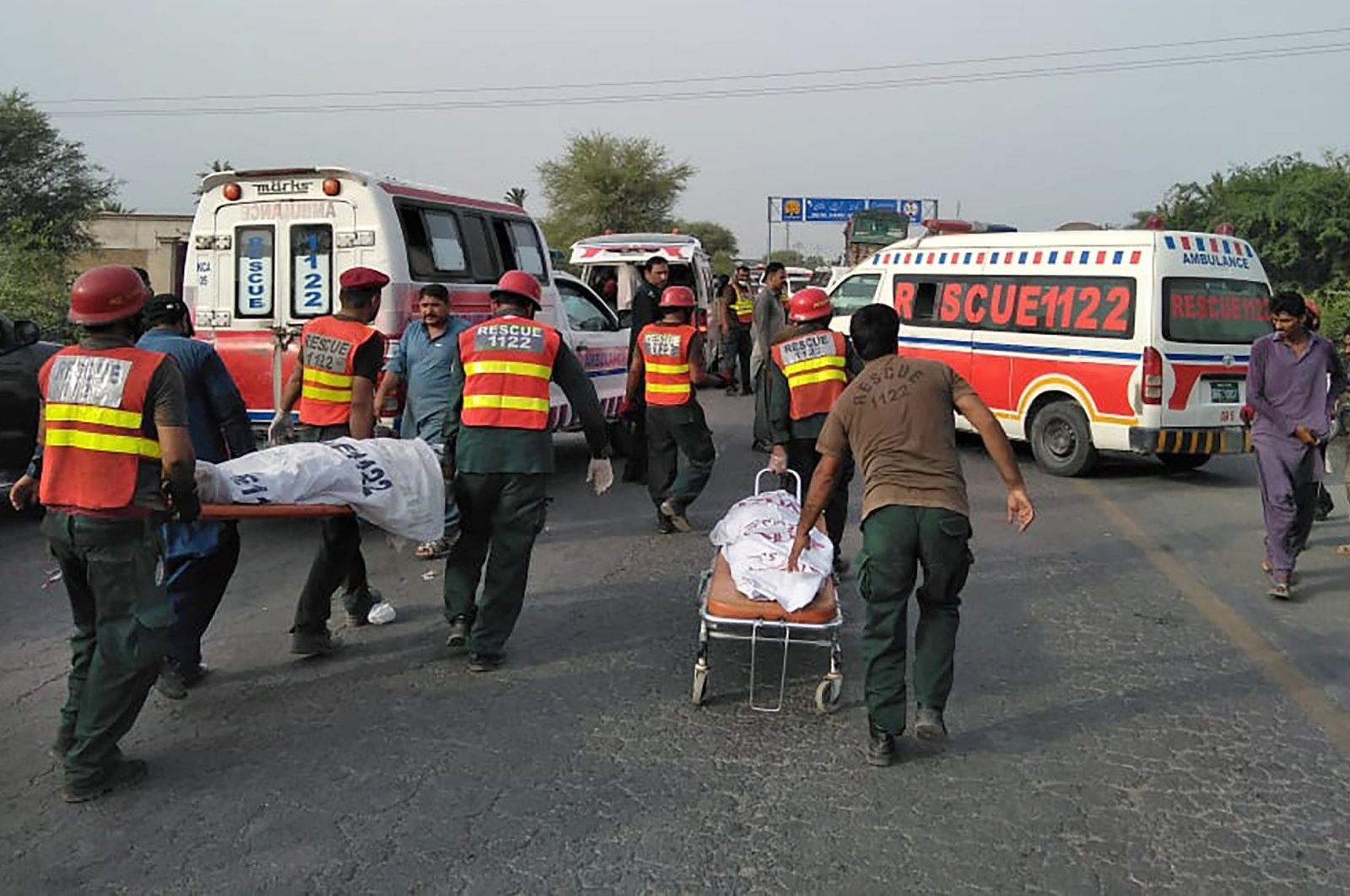 Rescue workers remove bodies at the site of a deadly bus accident near Dera Ghazi Khan, Pakistan, Monday, July 19, 2021. (Emergency Service Rescue 1122 via AP)