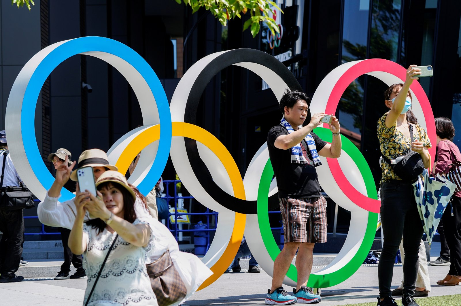 People take selfies in front of an Olympic Rings monument near the National Stadium, the main venue of the Tokyo 2020 Olympics and Paralympics in Tokyo, Japan, July 19, 2021. (Reuters Photo)