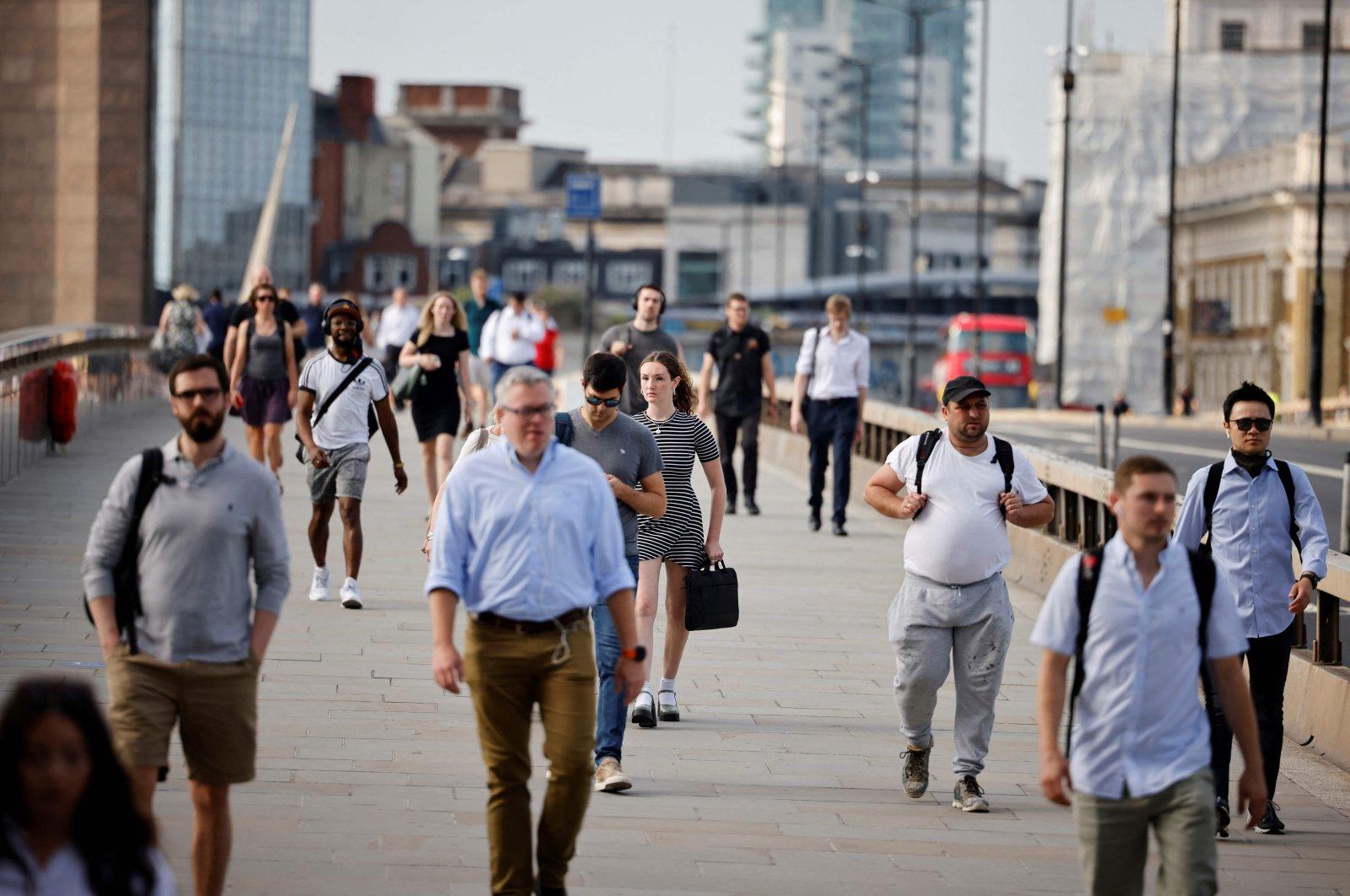Commuters not wearing facemasks cross London Bridge in London, U.K., July 19, 2021. (AFP Photo)