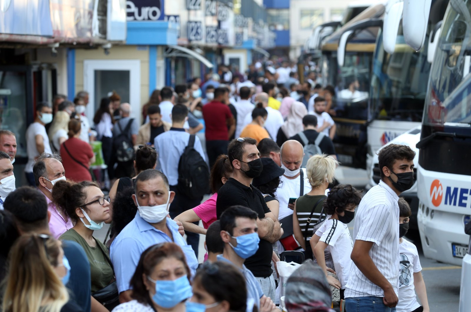 People wearing protective masks wait for buses at a bus terminal, in Istanbul, Turkey, July 18, 2021. (AA PHOTO)