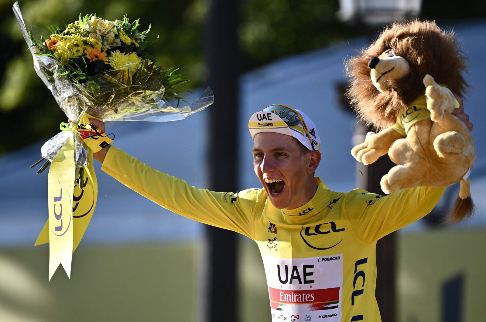 Team UAE Emirates' Tadej Pogacar of Slovenia celebrates his overall leader yellow jersey on the podium at the end of the 21st and last stage of the 108th edition of the Tour de France, July 18, 2021. (AFP Photo)