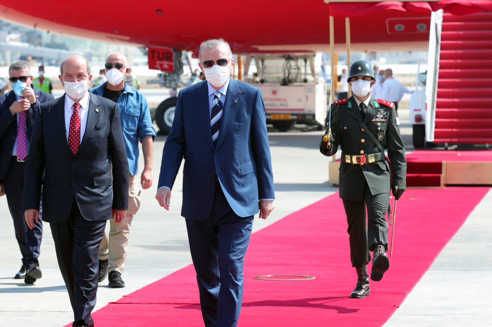 President Recep Tayyip Erdoğan (C) and his Turkish Cypriot counterpart Ersin Tatar walk on the red carpet during a welcoming ceremony at the Ercan Airport in Lefkoşa (Nicosia), Turkish Cyprus, on July 19, 2021. (AA Photo)