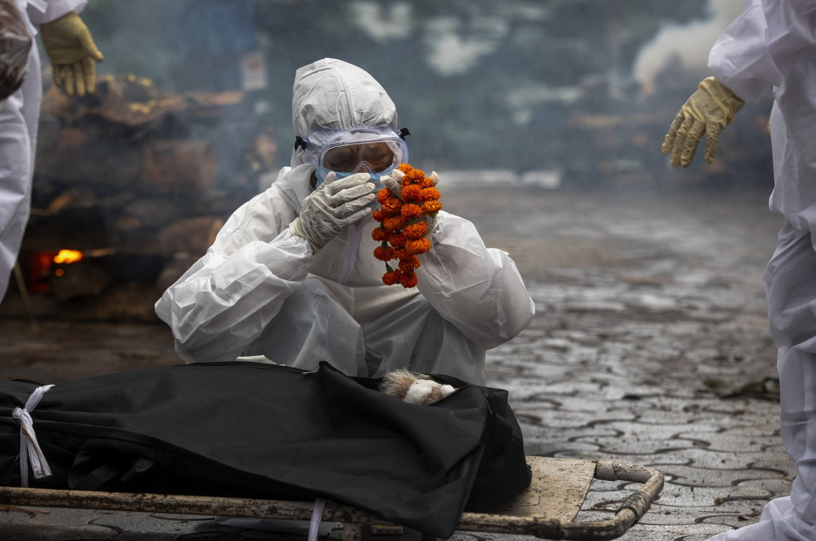 A relative performs last rites before the cremation of a COVID-19 victim in Gauhati, India, July 2, 2021. (AP Photo)