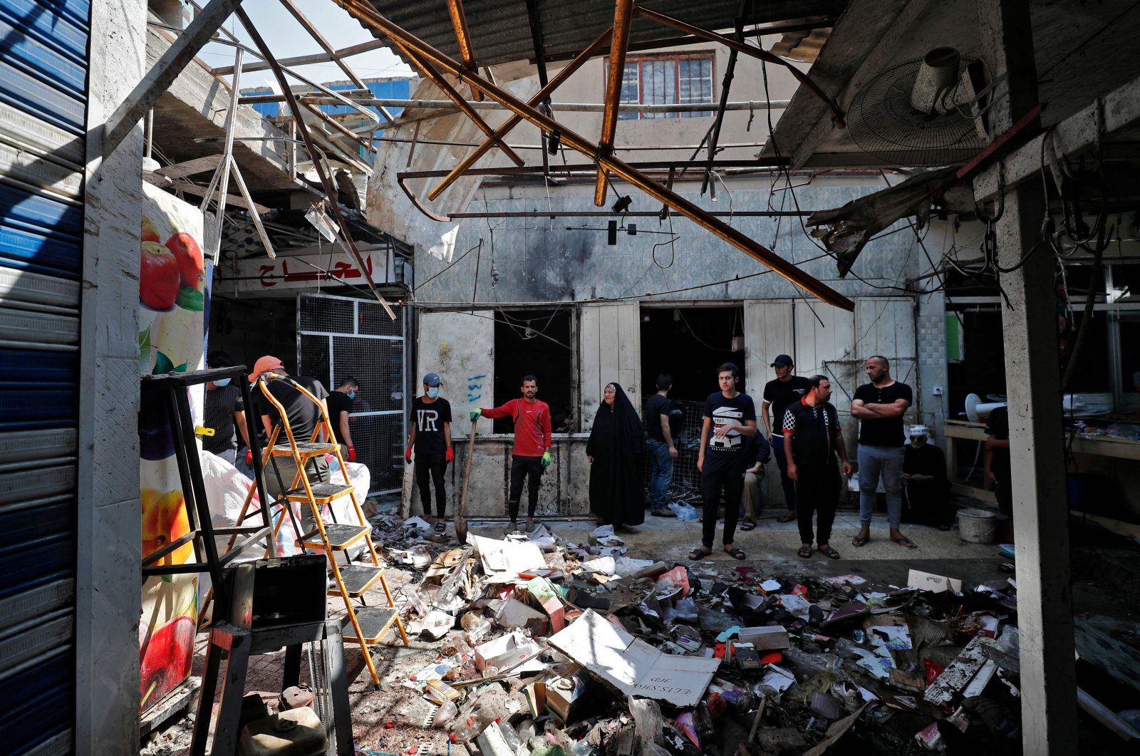 Iraqis inspect the site of the explosion a day earlier in a popular market in the Sadr City neighborhood, near capital Baghdad, Iraq, July 20, 2021. (AFP Photo)