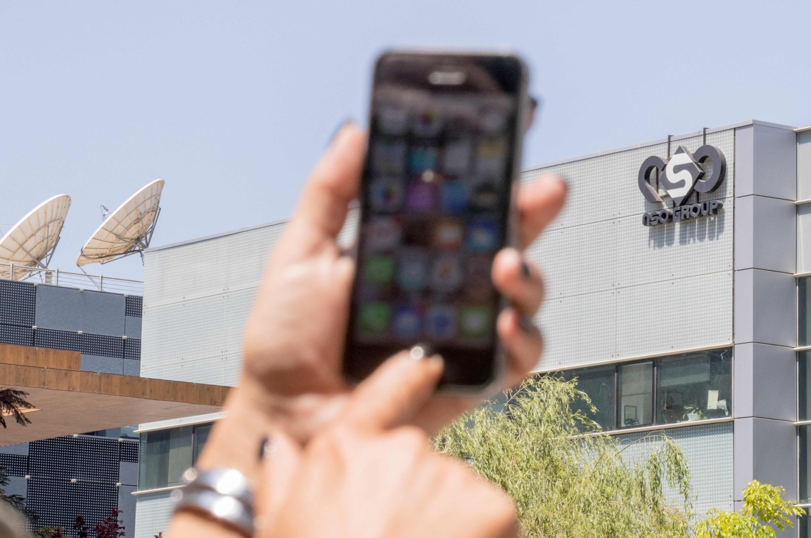 """A woman uses her iPhone in front of the building housing the Israeli NSO group """"Pegasus,"""" in Herzliya, near Tel Aviv, Israel, Aug. 28, 2016. (AFP Photo)"""