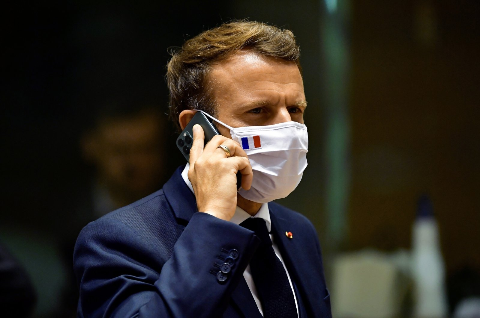 French President Emmanuel Macron speaks on his mobile phone during a round table meeting at an EU summit in Brussels, Belgium, July 20, 2020. (AP File Photo)