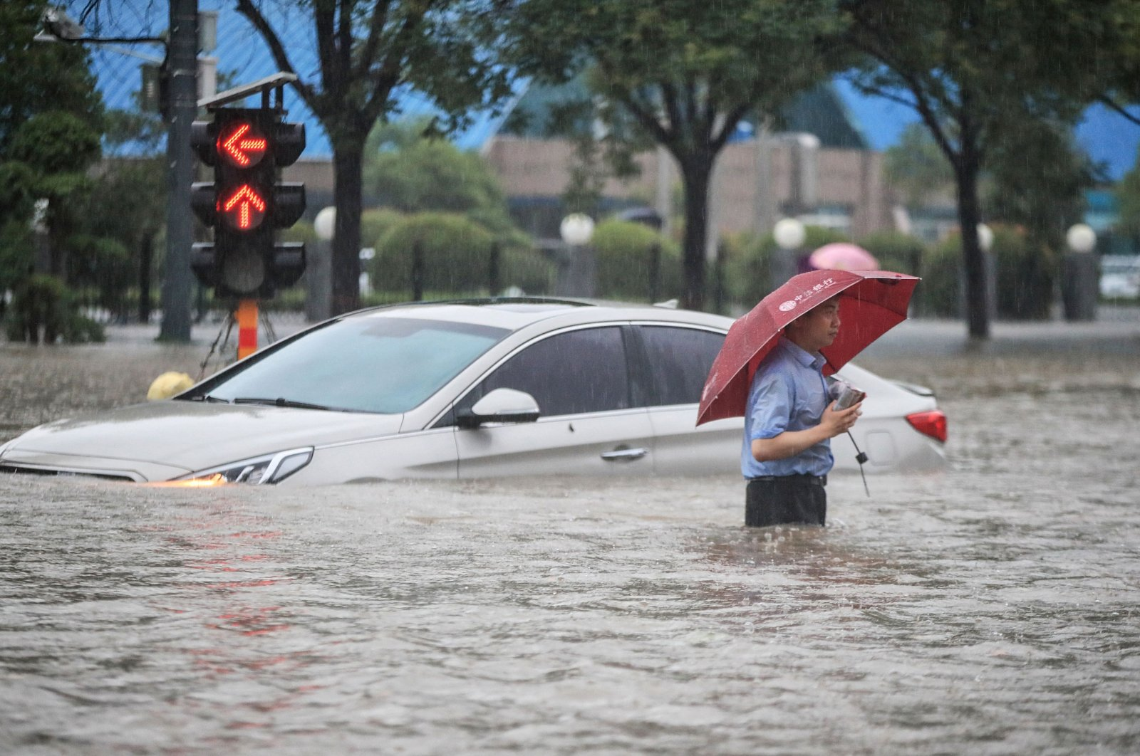 A man wades past a submerged car along a flooded street following heavy rains in Zhengzhou, China, July 20, 2021. (AFP Photo)