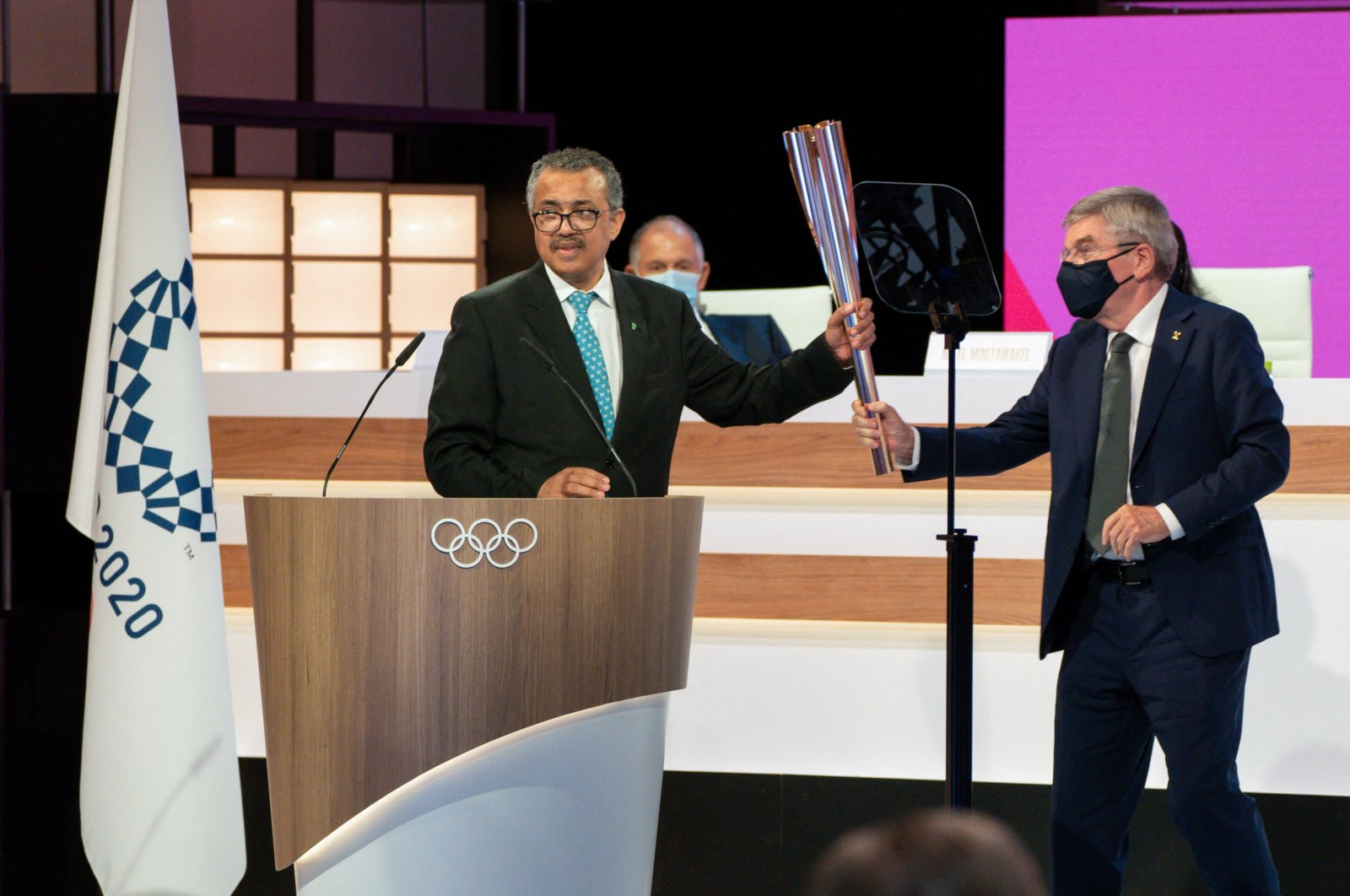 World Health Organization (WHO) Director-General Tedros Adhanom Ghebreyesus (L) receiving the Olympic torch from International Olympic Committee (IOC) President Thomas Bach during the second day of a IOC Session in Tokyo, Japan, July 21, 2021. (AFP Photo)
