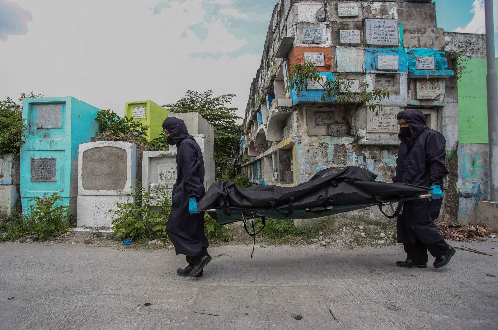 Workers wearing masks, gloves and protective coats carry a body bag containing the skeletal remains of Rodzon Enriquez, who was killed five years ago in the country's war on drugs, after they were exhumed at a cemetery in Manila, the Philippines, July 8, 2021. (AFP Photo)