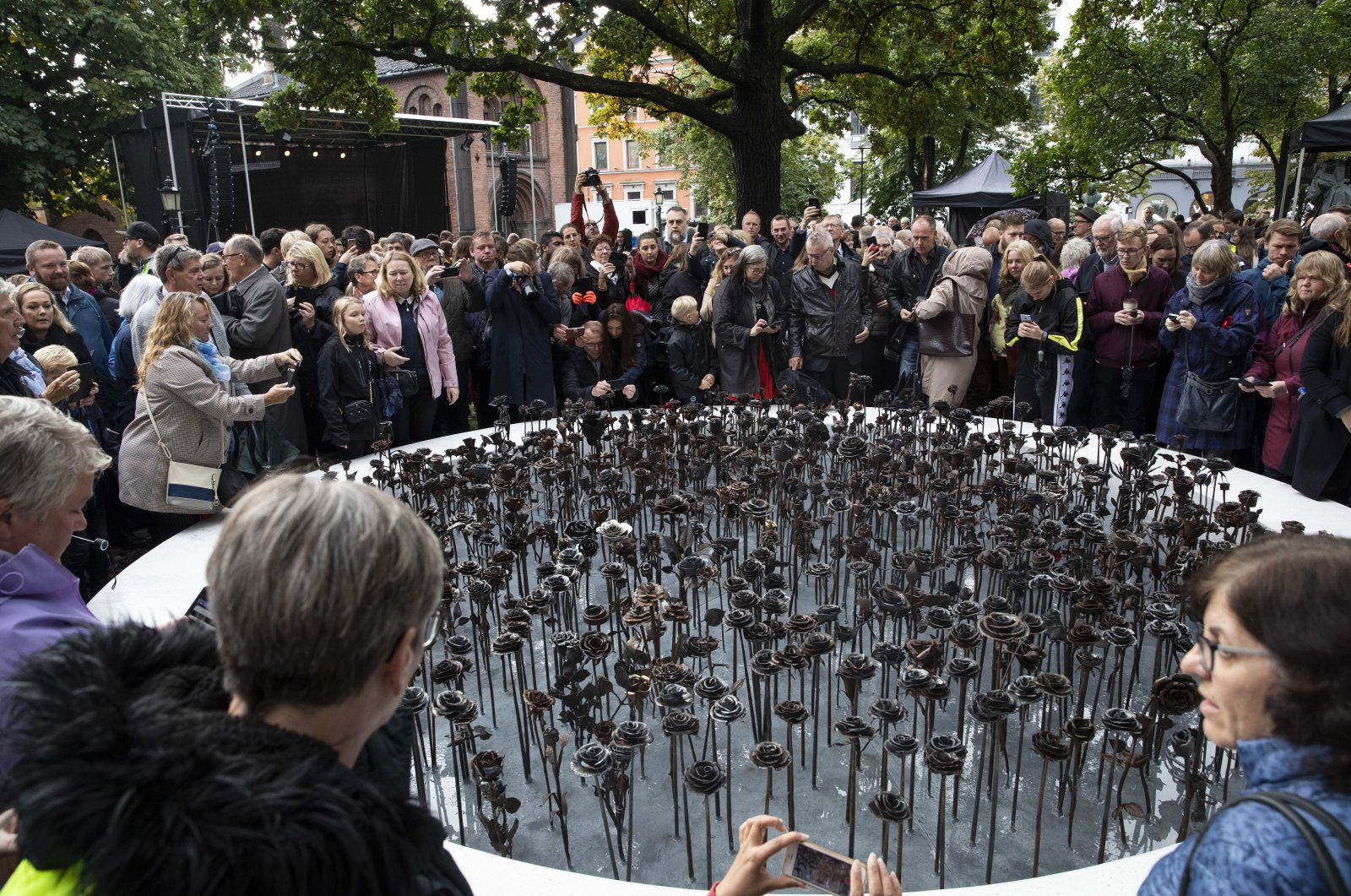 """People look at the """"Iron roses"""" memorial dedicated to 77 people who lost their lives to the 2011 terrorist attacks, in Oslo, Norway, Sept. 28, 2019. (AP Photo)"""