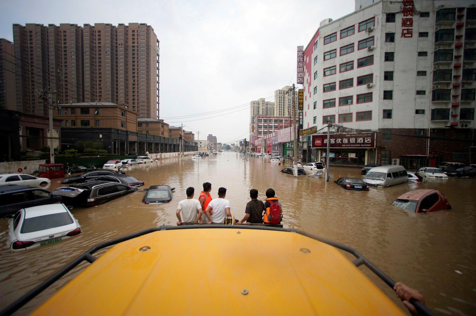 People ride a front loader as they wade through a flooded road following heavy rainfall in Zhengzhou, Henan province, China, July 22, 2021. (Reuters Photo)